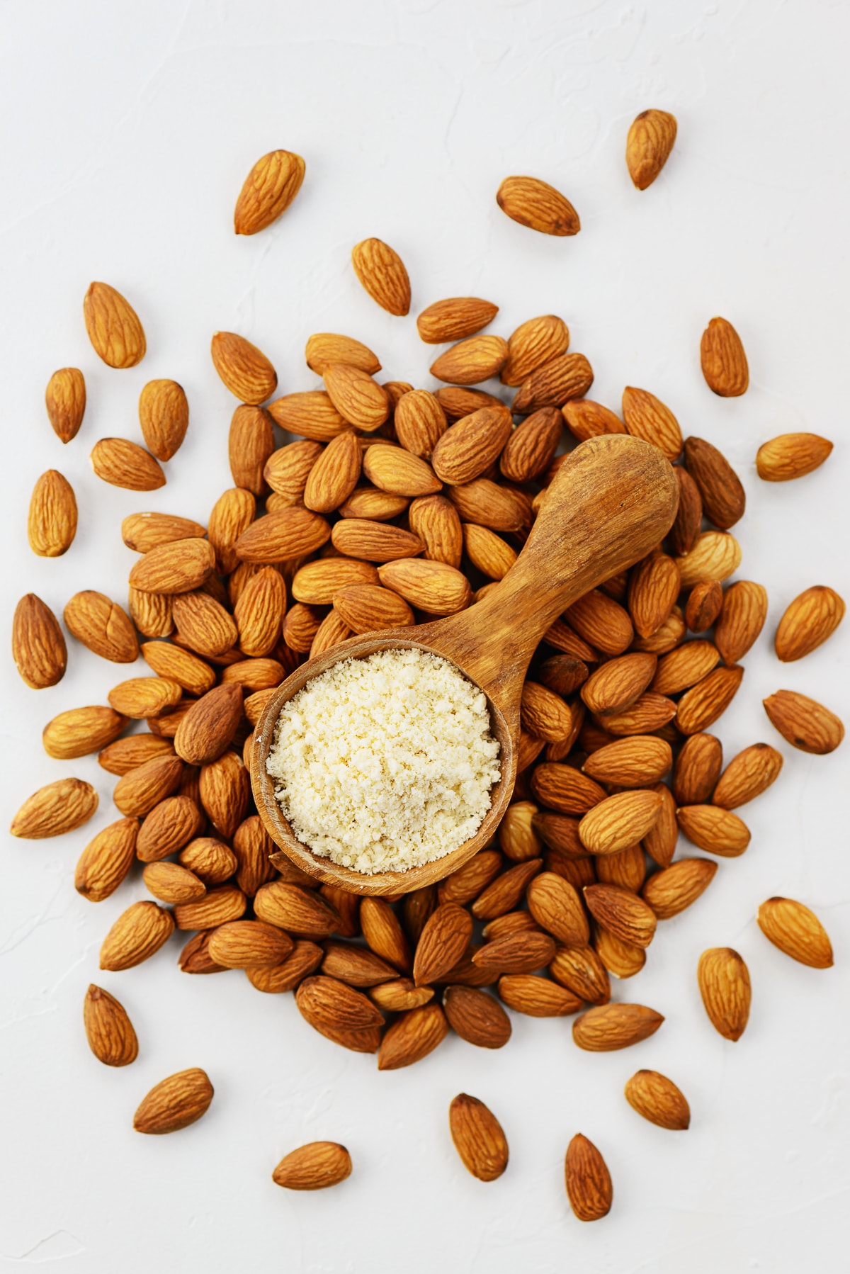 A pile of whole almonds with a wooden spoon filled with almond flour