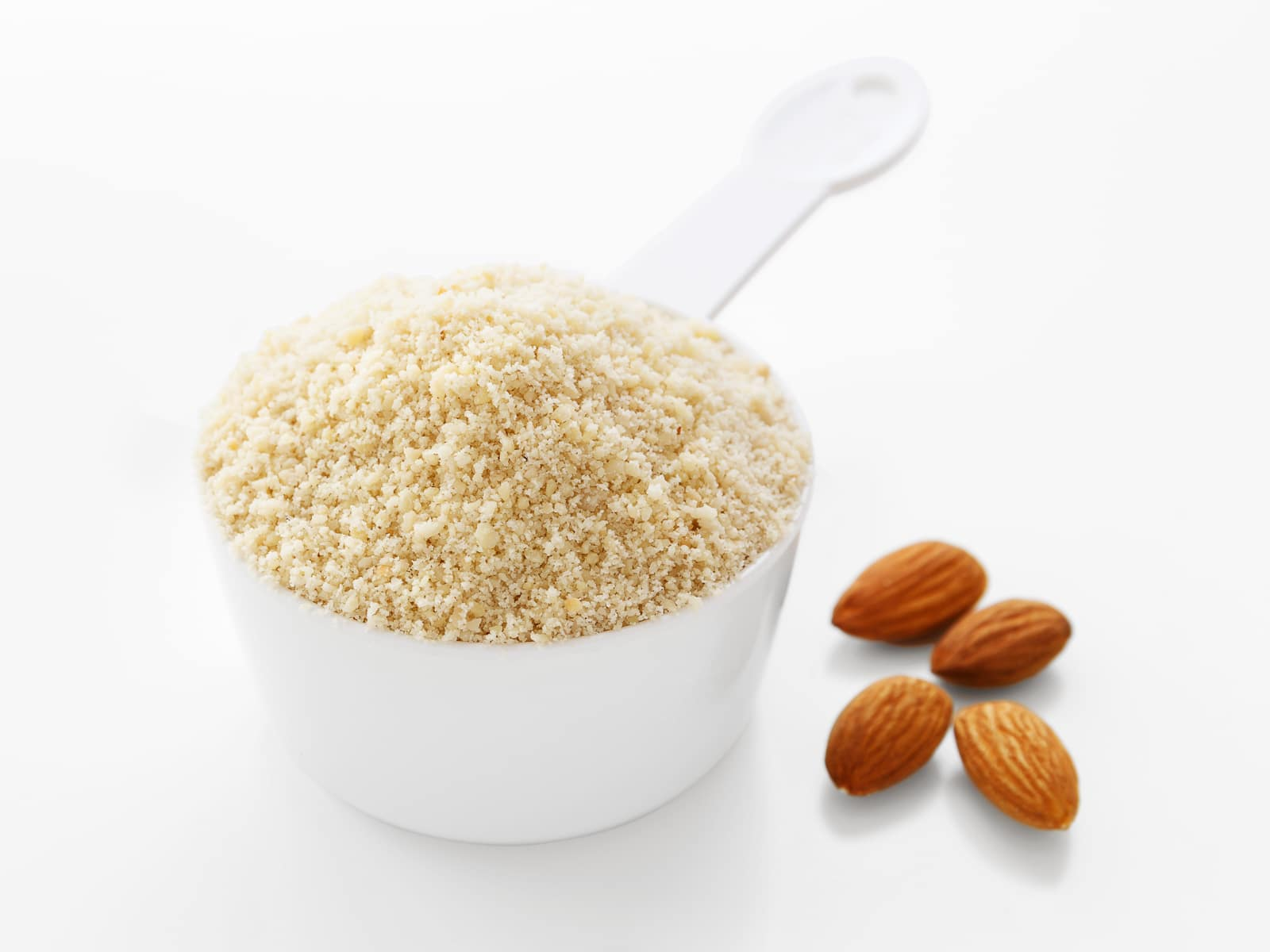 A measuring cup filled over the brim with almond flour
