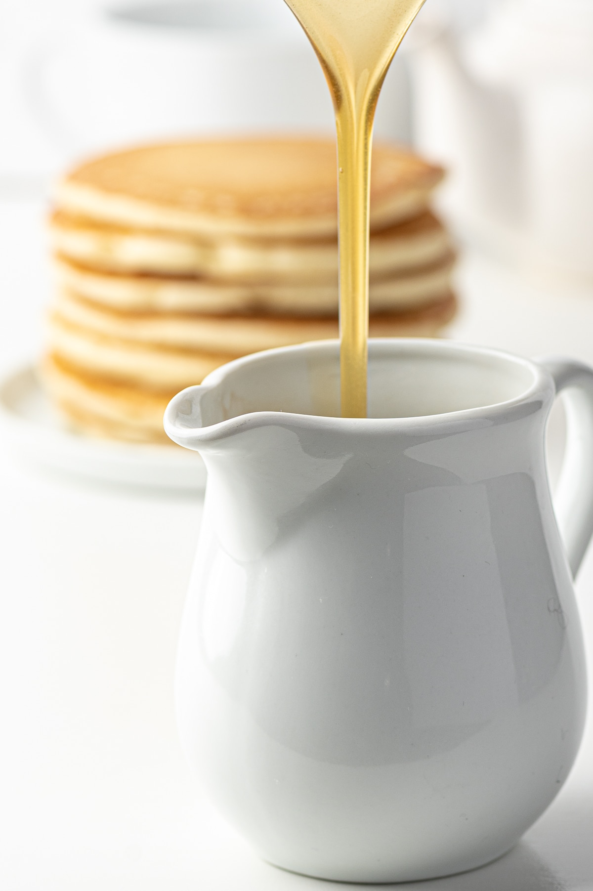 A stream of golden pancake syrup being poured into a white dish.  A stack of pancakes in the background slightly out of focus.