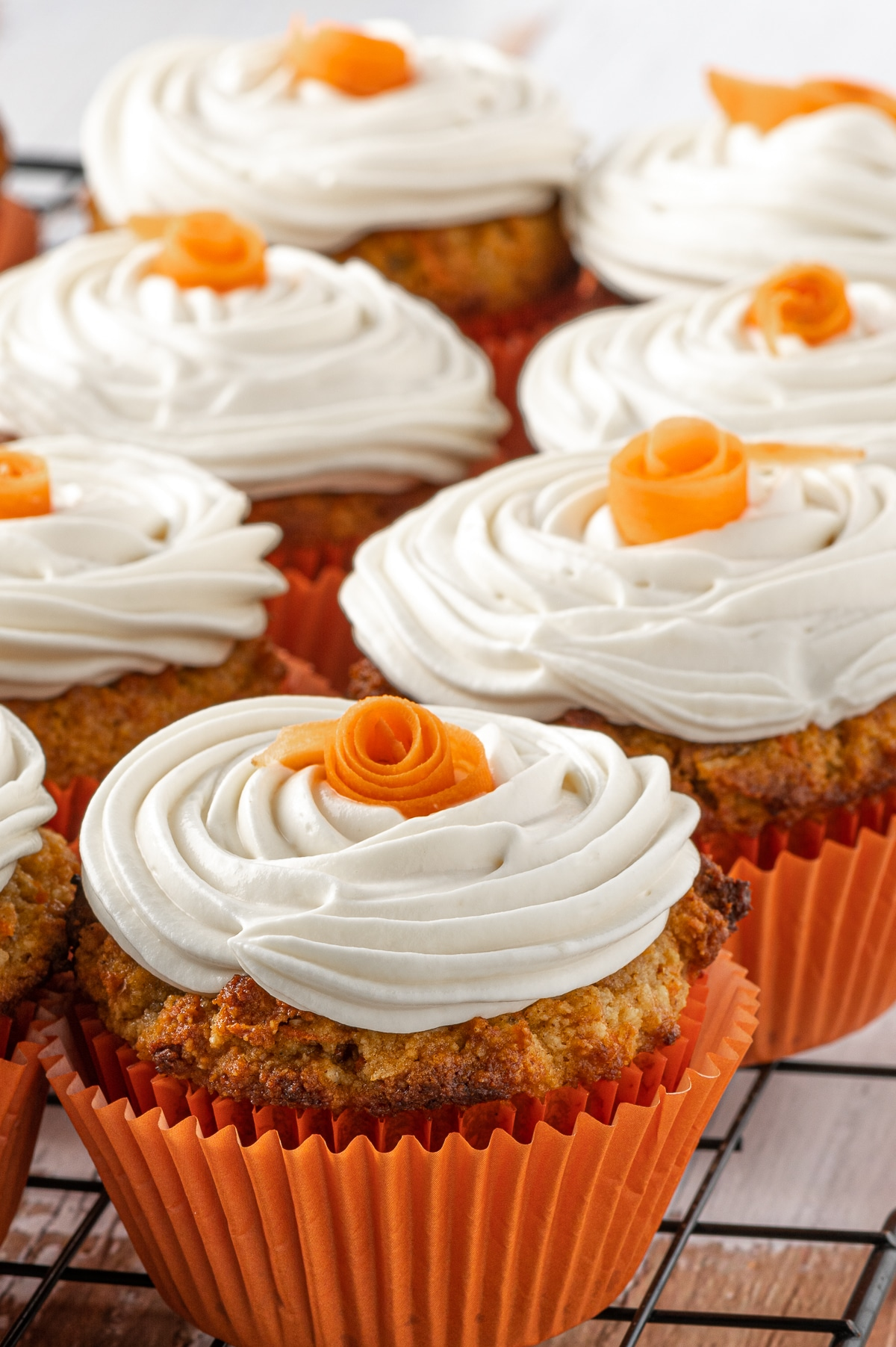 Close up of a batch of low carb carrot cake muffins with swirls of cream cheese frosting and small orange roses on the top.