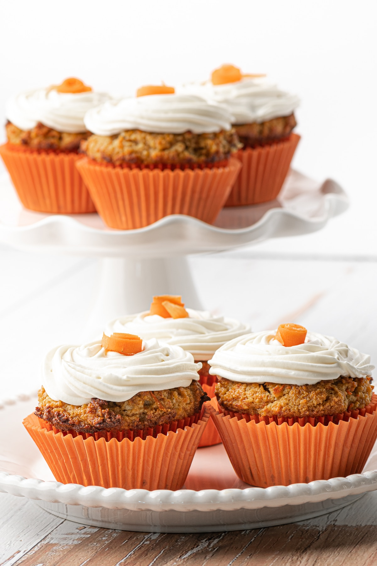 White plate with three muffins in the foreground and a stack of carrot cake muffins on a white ruffled cake stand in the back