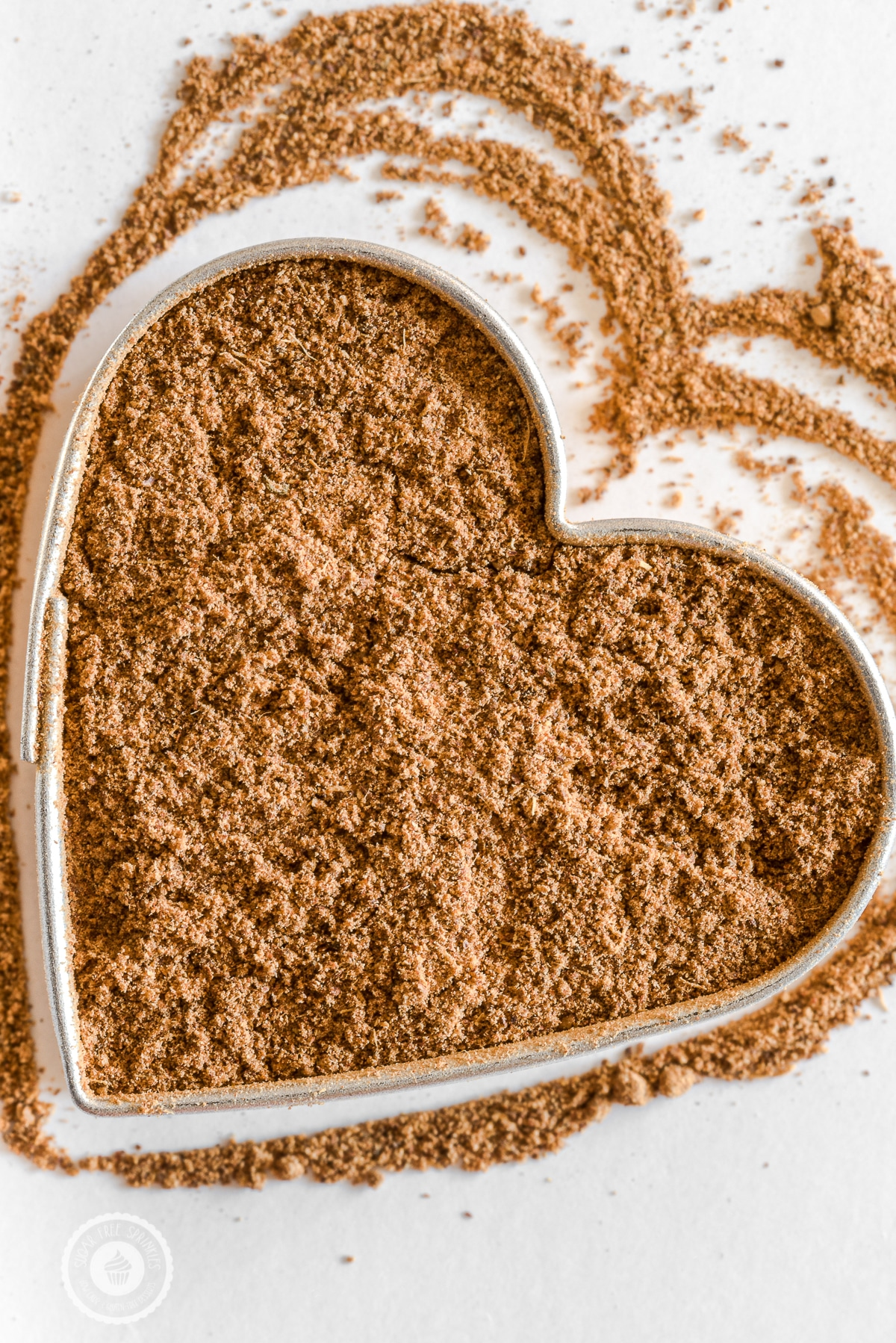 A heart shaped cookie cutter filled with a pumpkin pie spice blend on a bright white background