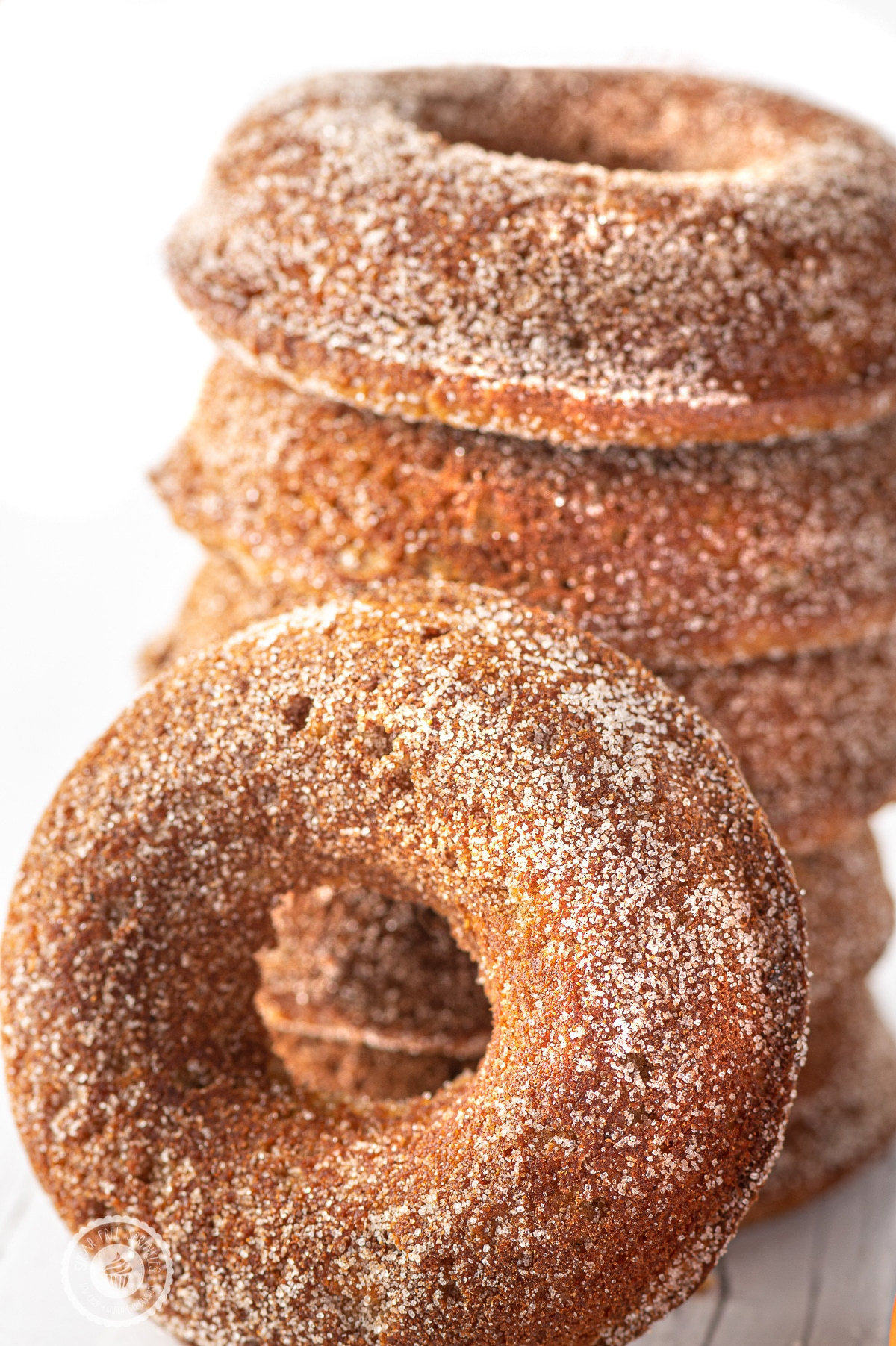 A stack of golden brown sugar coated keto pumpkin spice donuts against a bright white background.