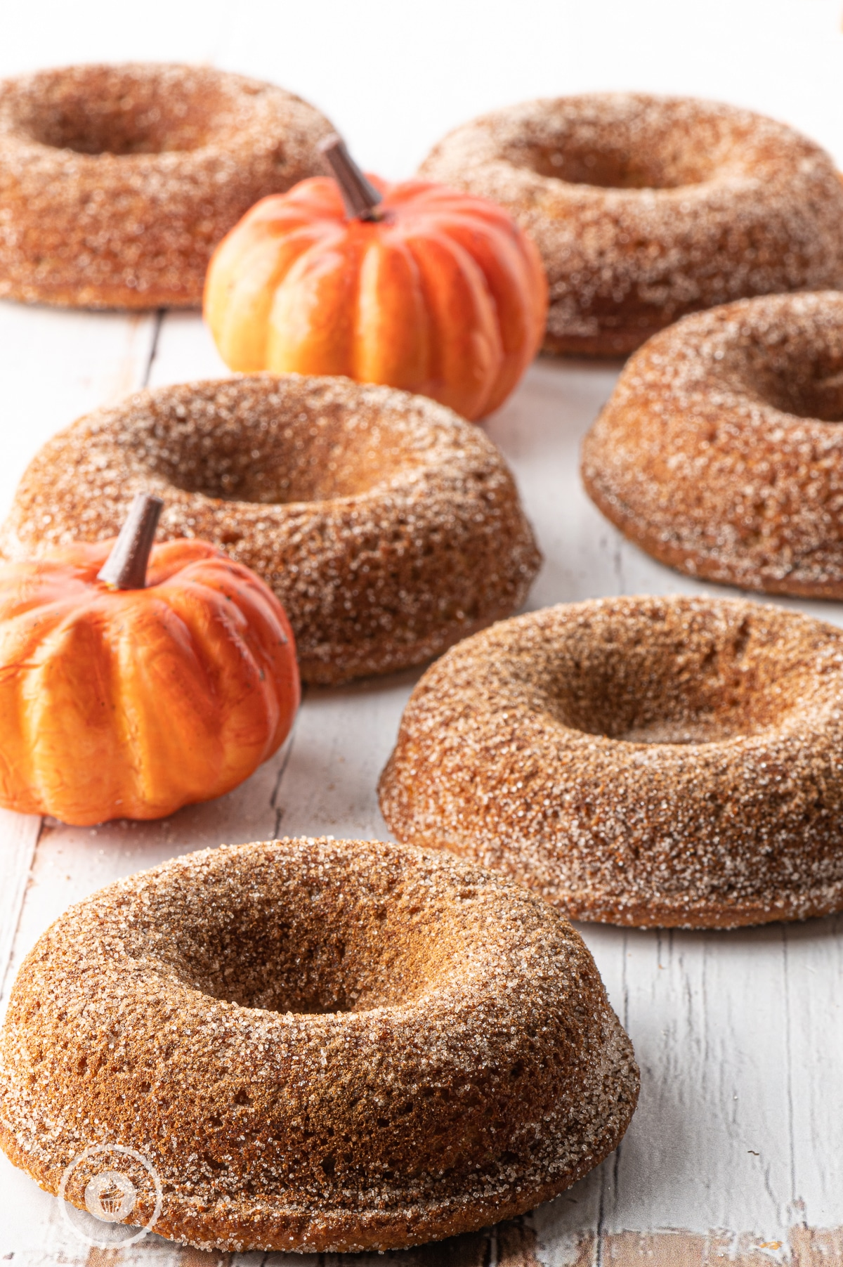 Pumpkin donuts laid out on a white rustic wooden table with mini orange pumpkins scattered around.