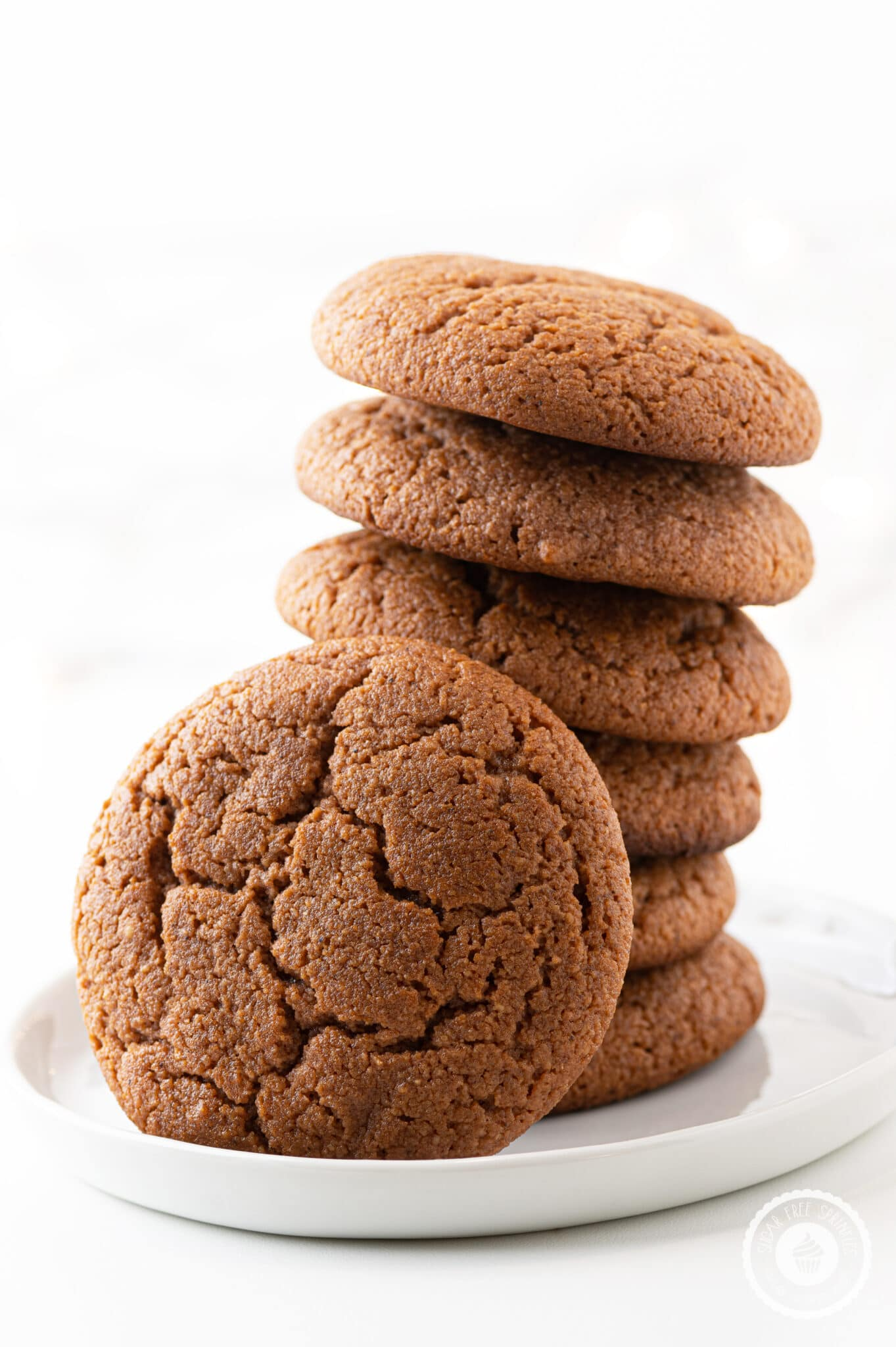 A stack of keto gingerbread cookies on a white plate against a bright white background.