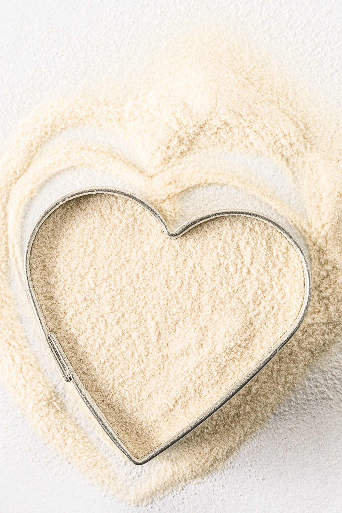 Xanthan gum spread on a bright white table with a silver heart cookie cutter.