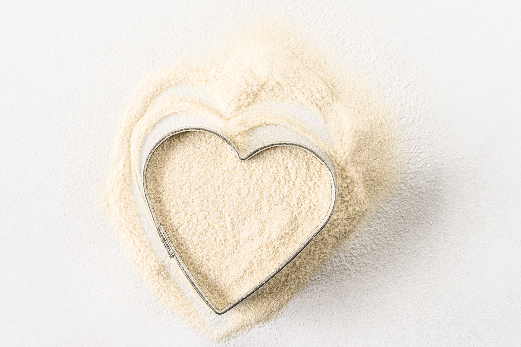 A small metal heart shaped cookie cutter filled with white powdered xanthan gum.