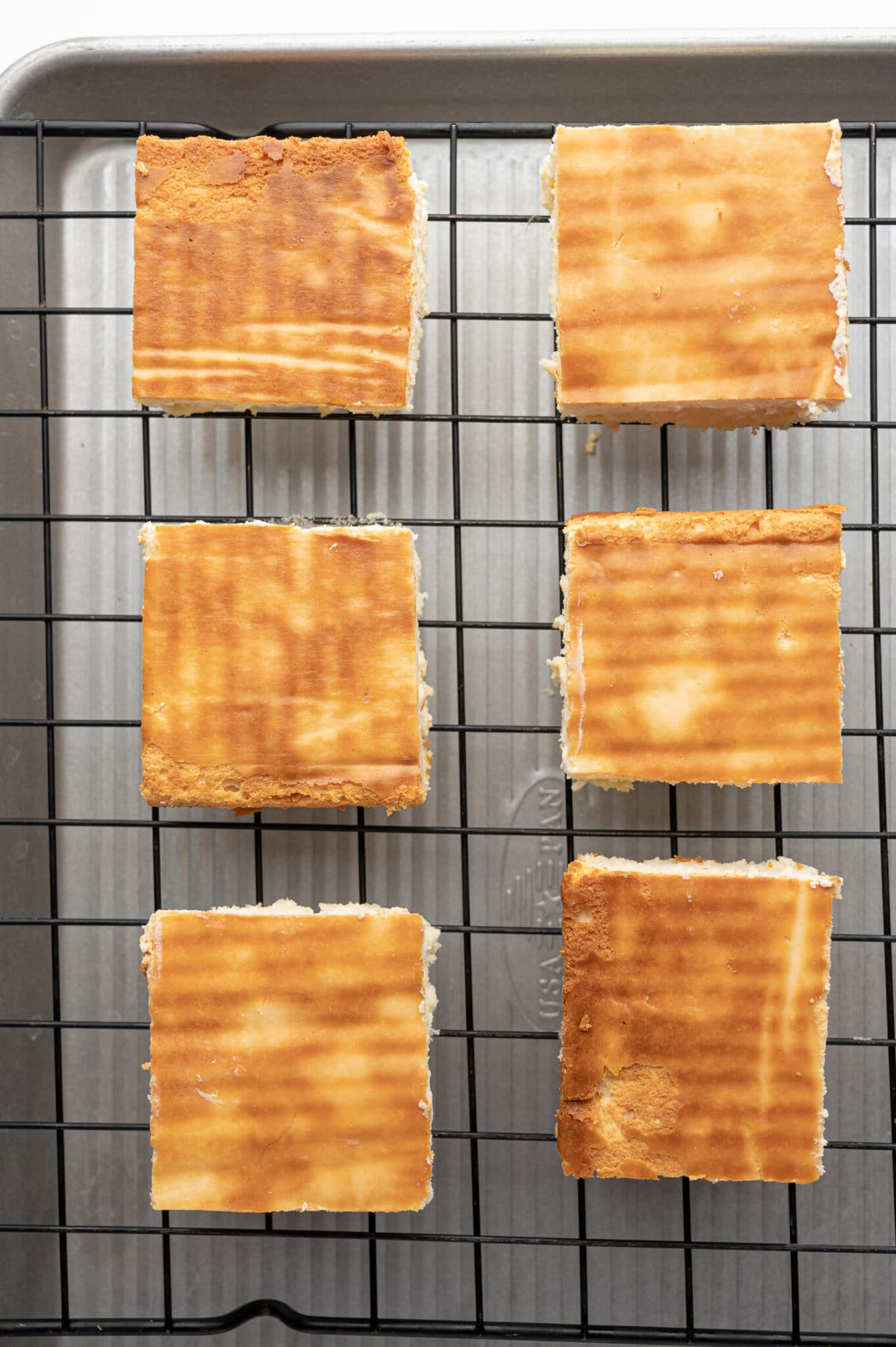 Cute square of baked cheesecake on a cooling rack