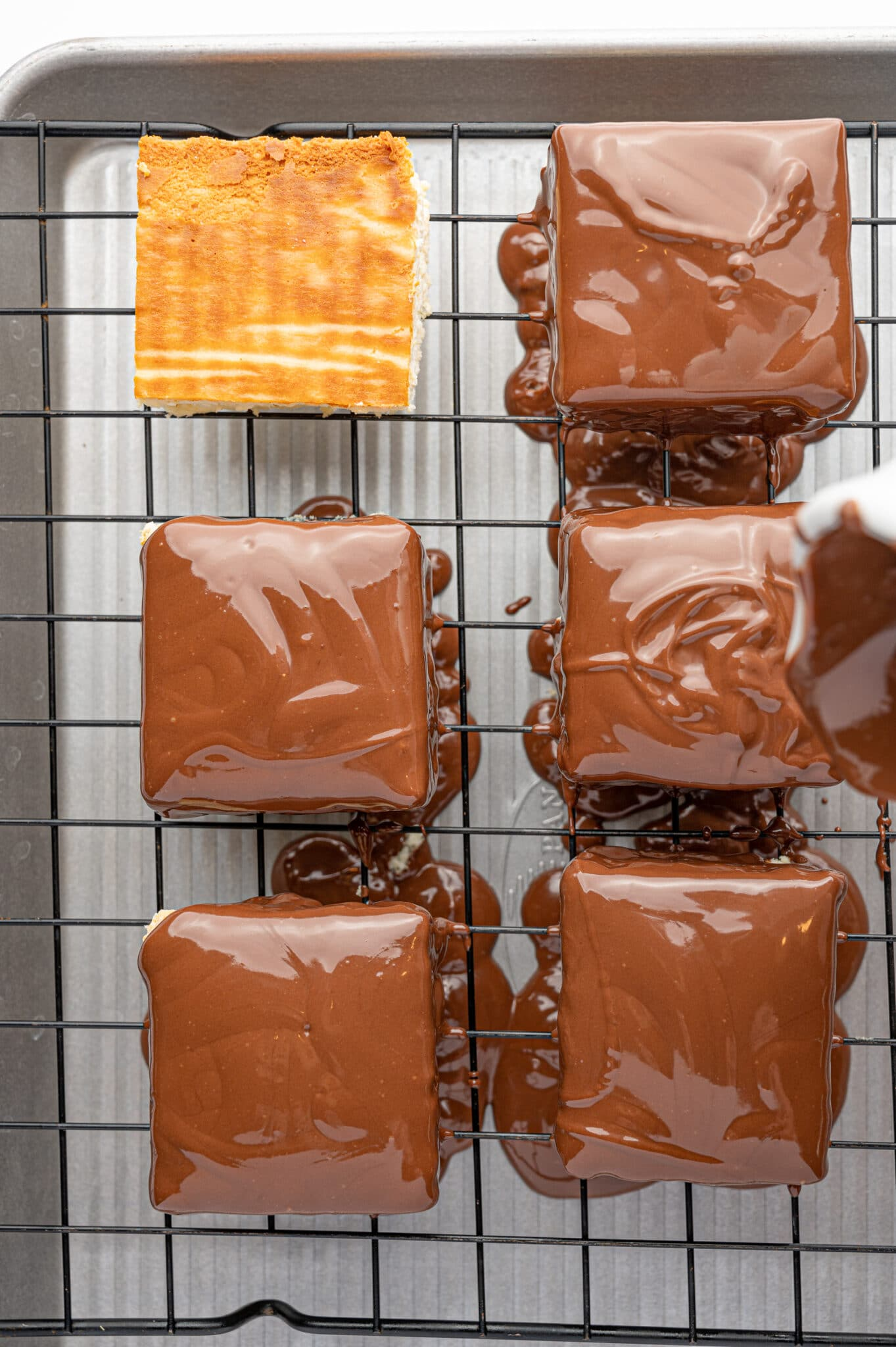 Square pieces of keto cheesecake bites being coated with melted milk chocolate.