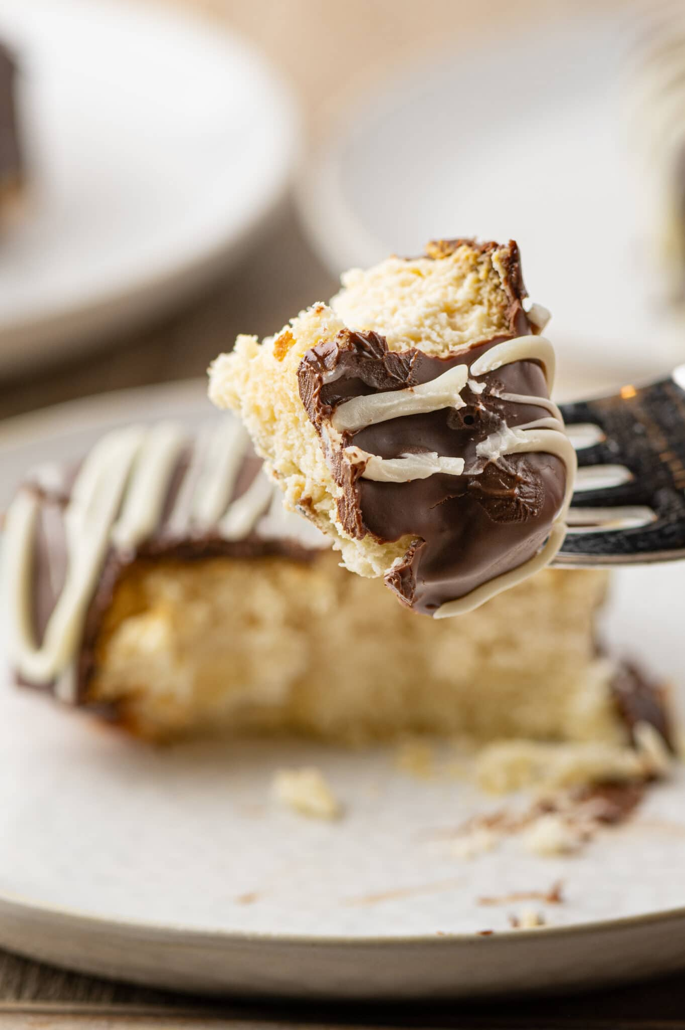 A fork with a piece of keto cheesecake bite coated in chocolate.