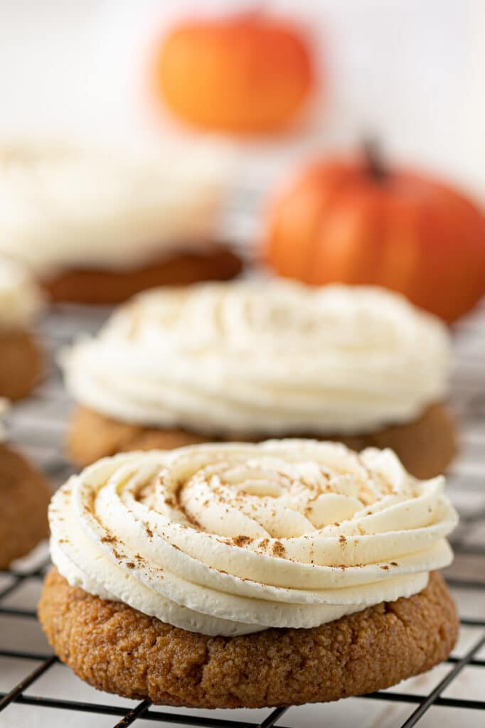 A low carb pumpkin cookie with a swirl of cream cheese frosting.  Mini pumpkins are in the background.