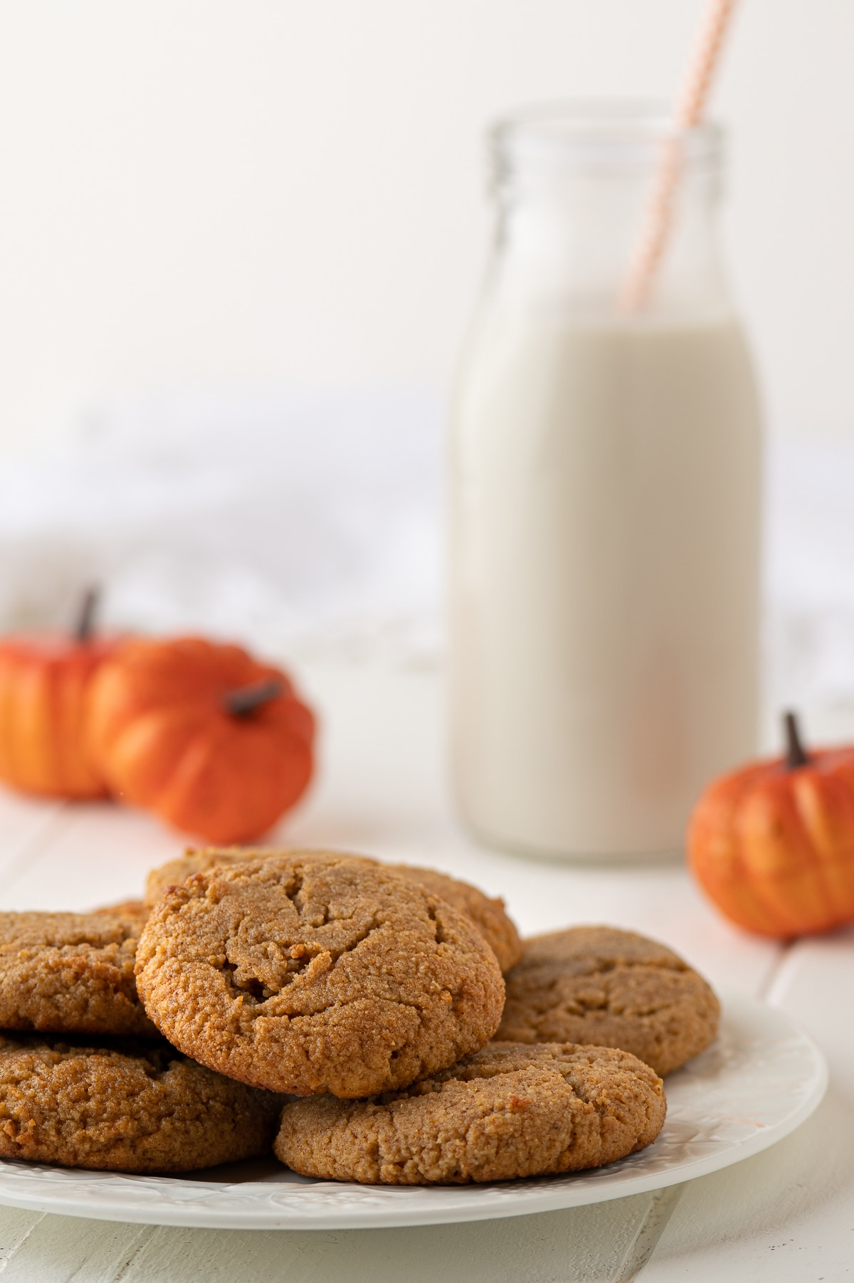 Pumpkin cookies on a white plate with a glass of almond milk and mini orange pumpkins in the background