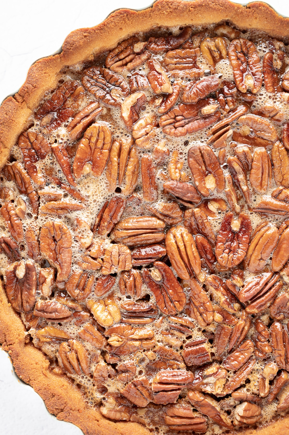 a close up image of the top of a pecan pie showing the sticky gooey texture of the filling and golden baked pecans in a perfectly baked crust.