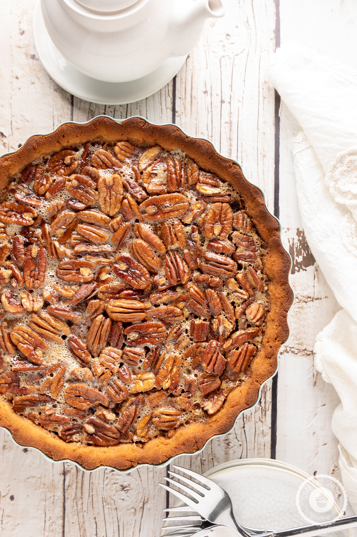 Pecan pie on a rustic wooden backdrop with white napkin, plates and a pot of hot tea