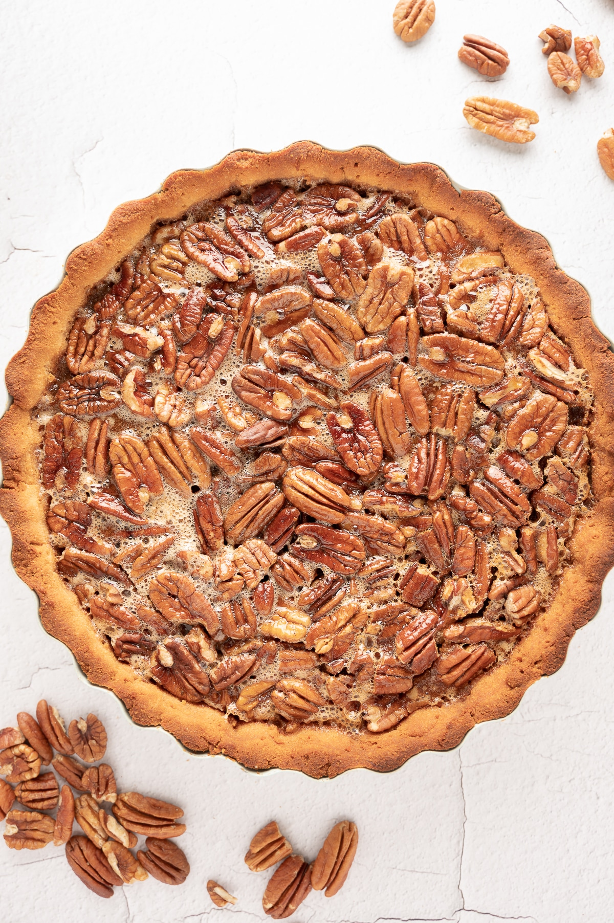sugar-free pecan pie on a bright white back ground with scattered raw pecans.