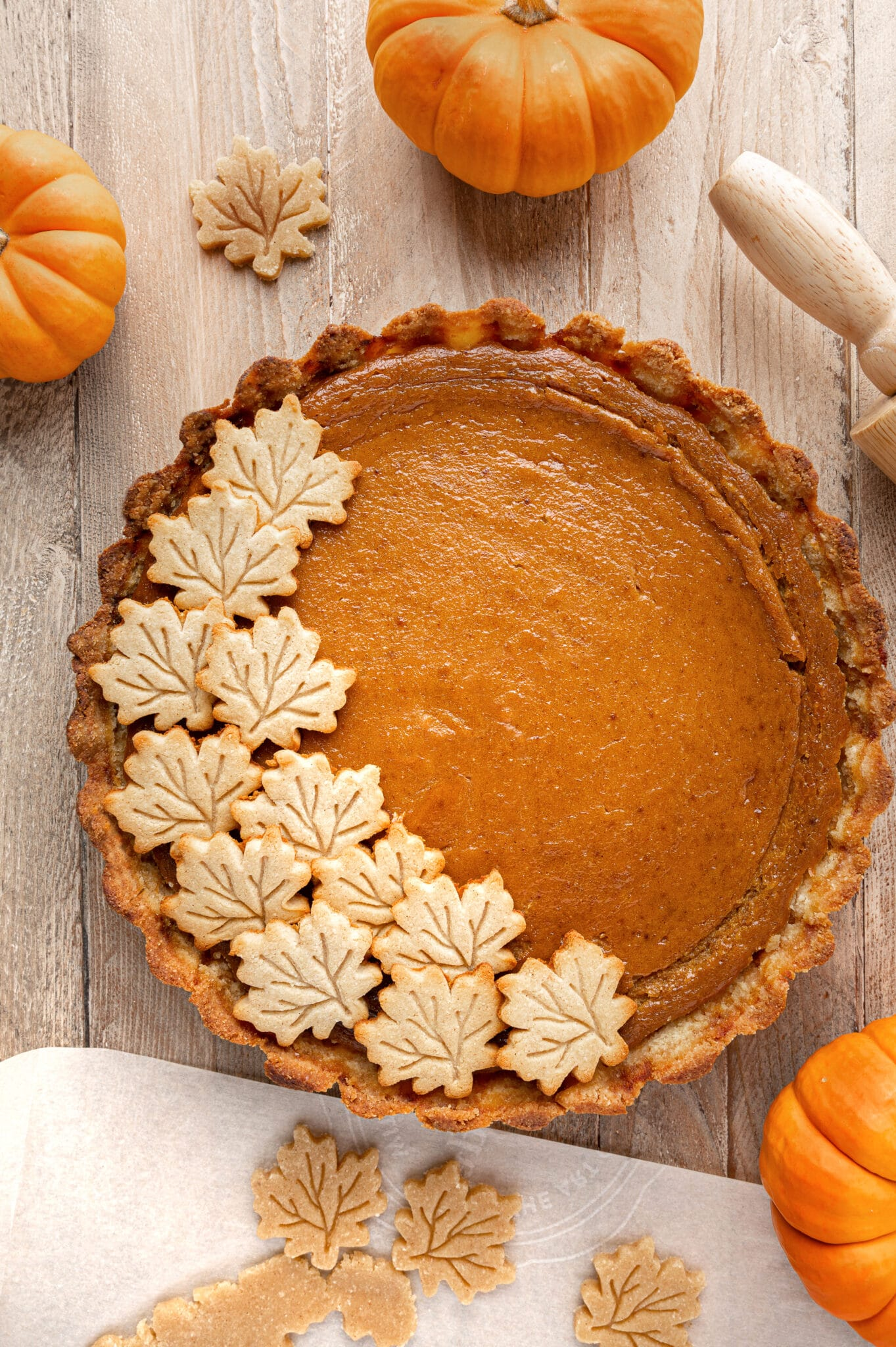 Pumpkin pie with maple shaped decorations on a rustic wooden background surrounded by mini orange pumpkins.