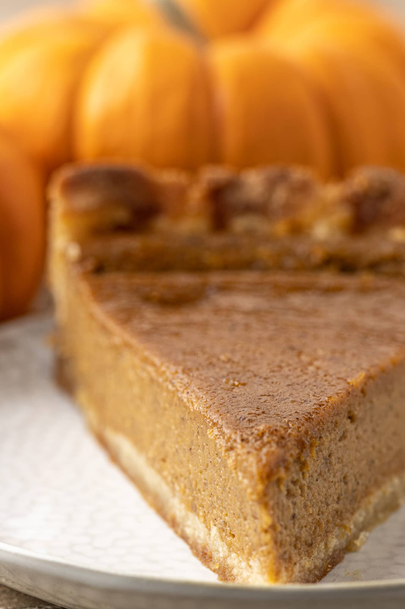 A slice of pumpkin pie with orange pumpkins in the background