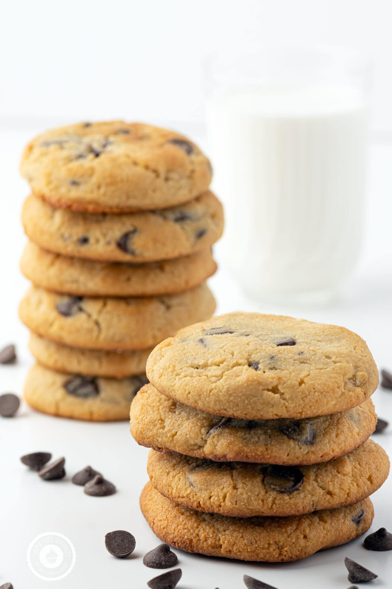 Stacks of  chocolate chip cookies on a white background with scattered chocolate chips and a glass in the background filled with milk.