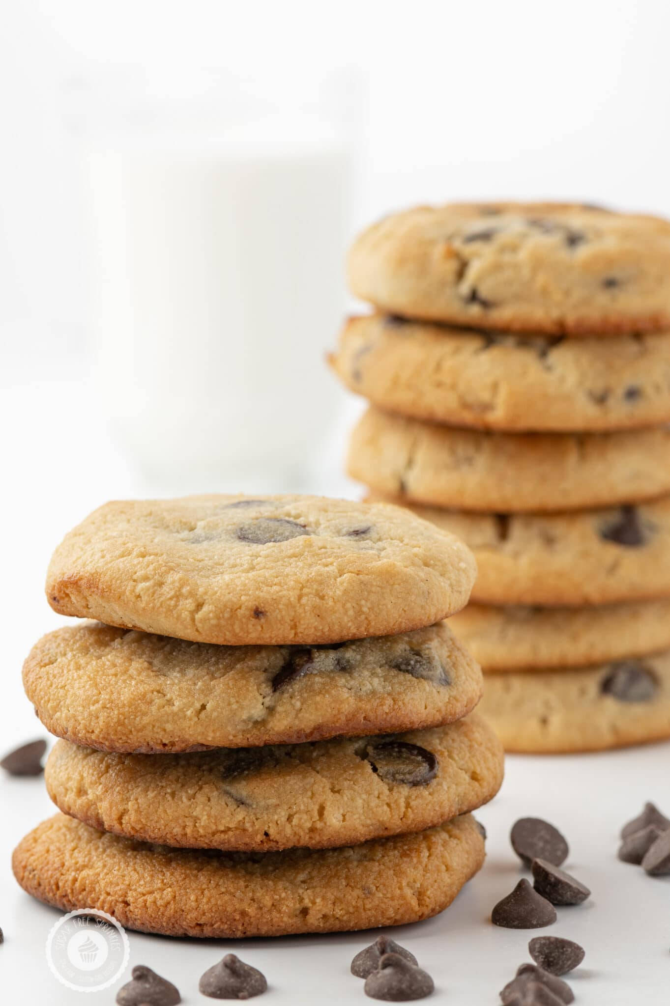 Stacks of keto chocolate chip cookies on a white background with scattered chocolate chips and a glass in the background filled with almond milk.