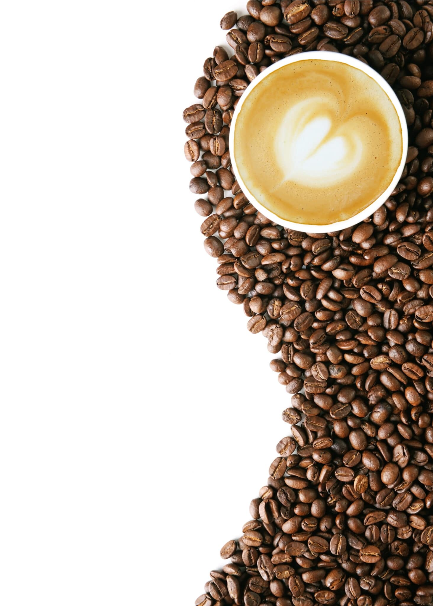Coffee beans on a bright white table top with a cup of coffee with a white foam heart in the center.