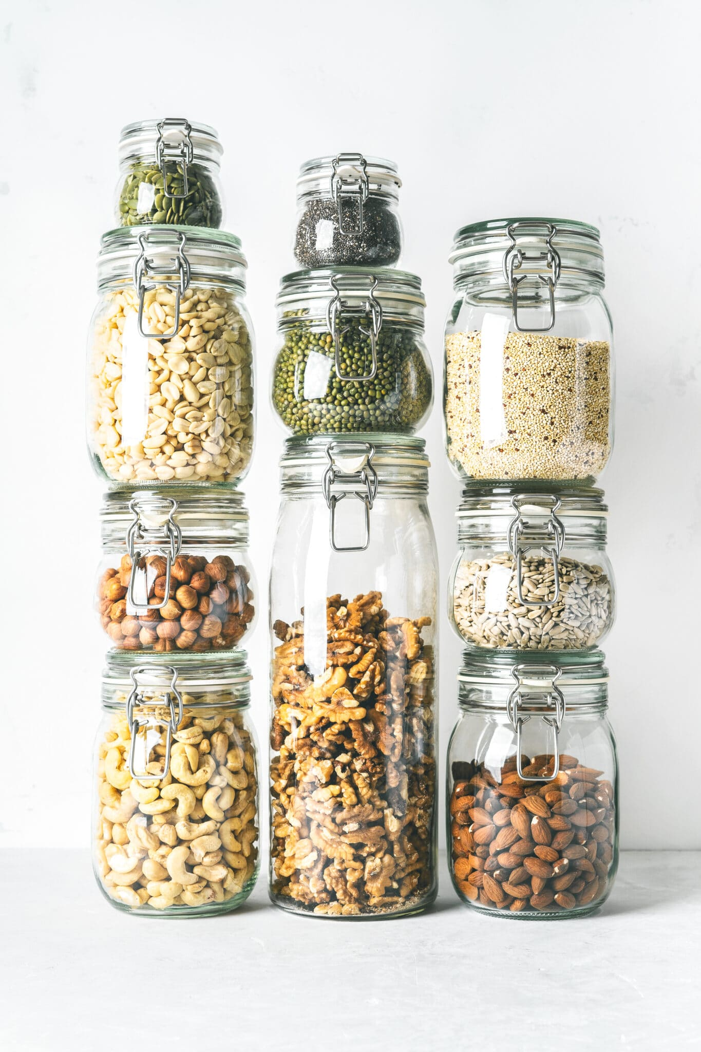 Glass jars stacked filled with low carb panty essential nuts and seeds