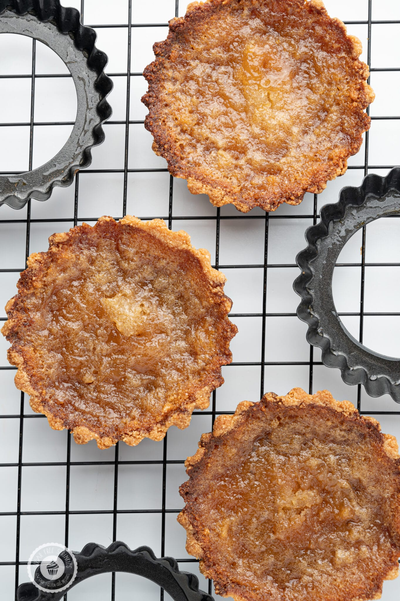 Sugar-free butter tarts cooling a black cooling rack with the metal tart pans scattered around.