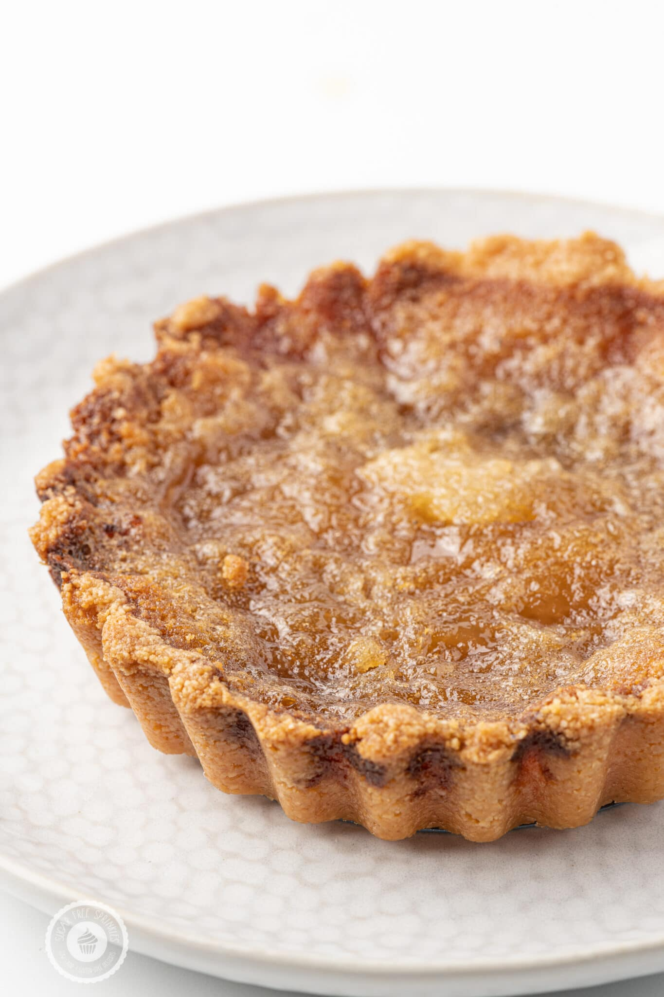 Golden brown sugar-free butter tart on a white plate against a bright white background.