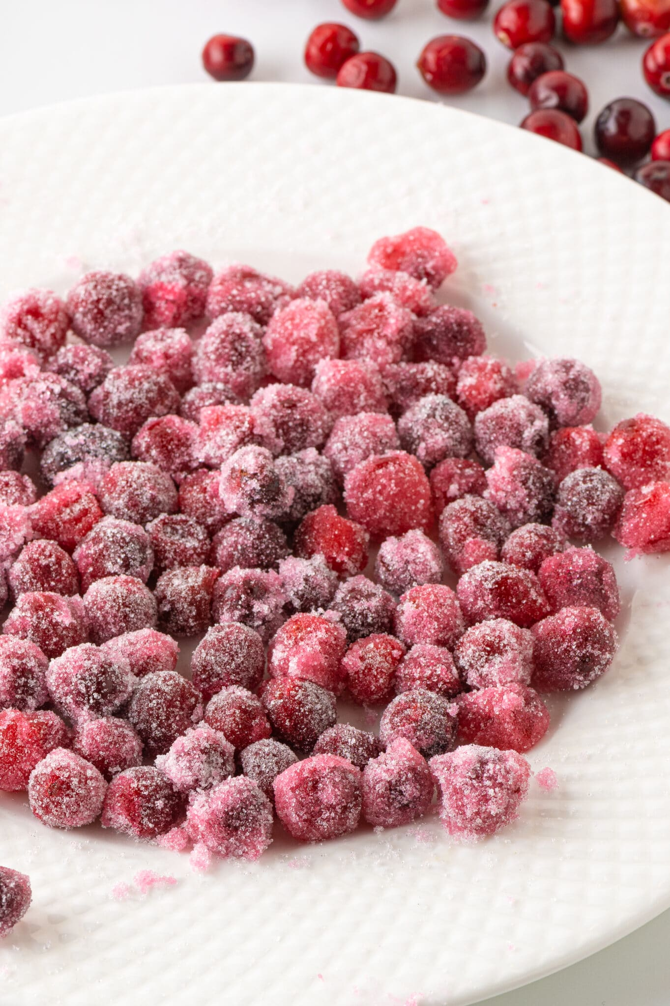 A white plate filled with red ripe cranberries coated in granular sweetener.  The berries look like they have been covered in a pink winter frost.