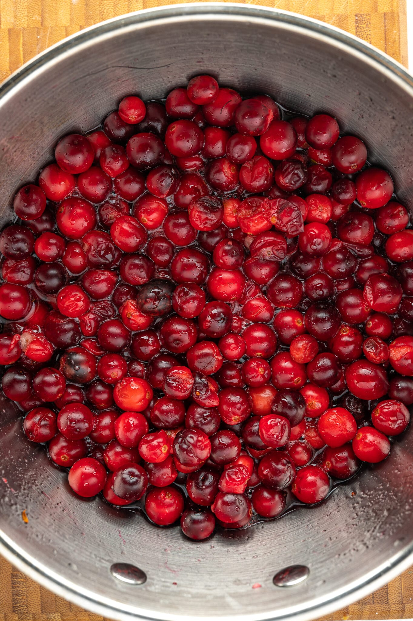 A pot of red ripe cranberries cooking in sugar-free syrup.  A few of the berries have cracked.