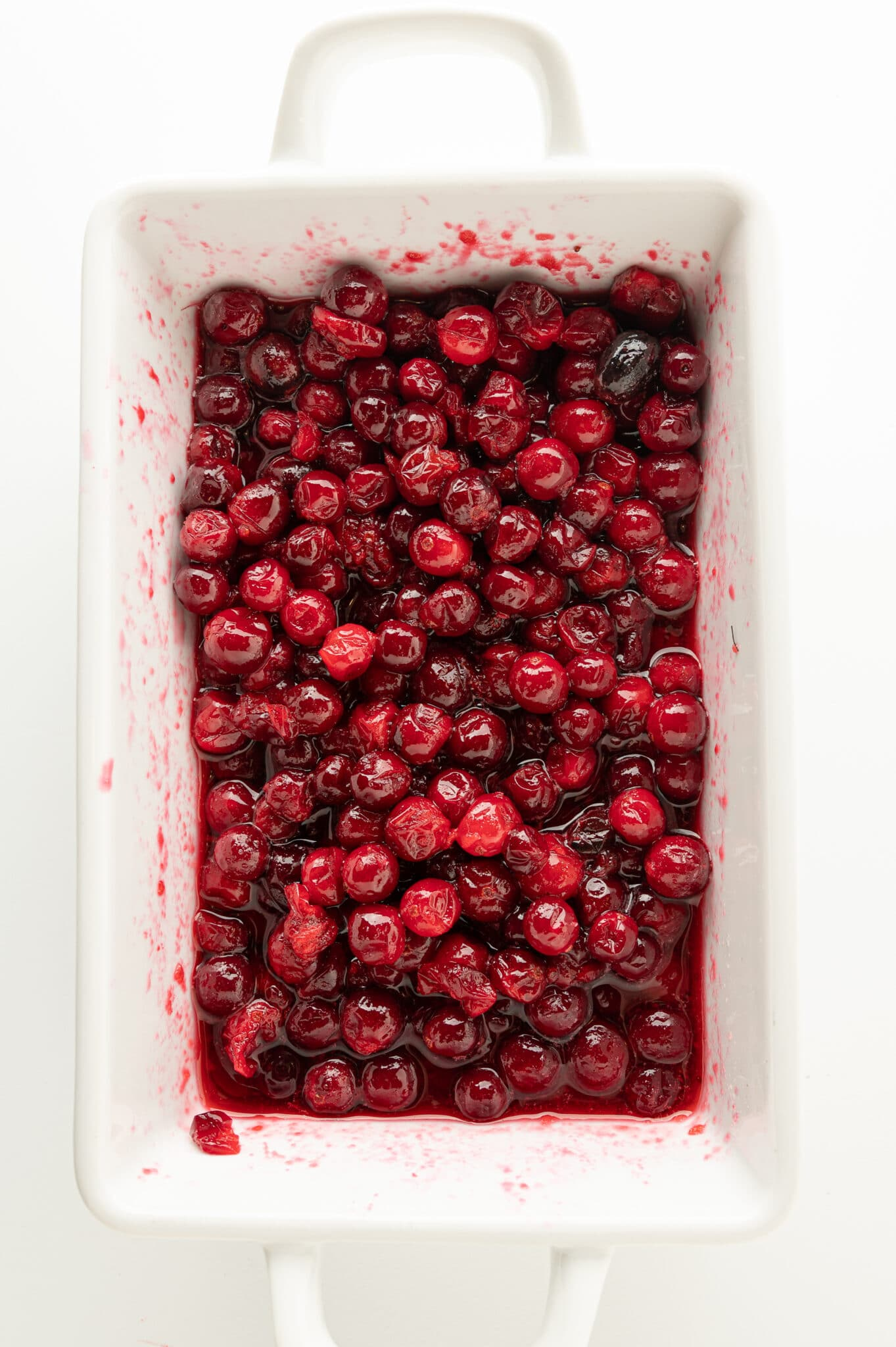A white dish filled with ruby red berries glossy coated with a thick syrup.