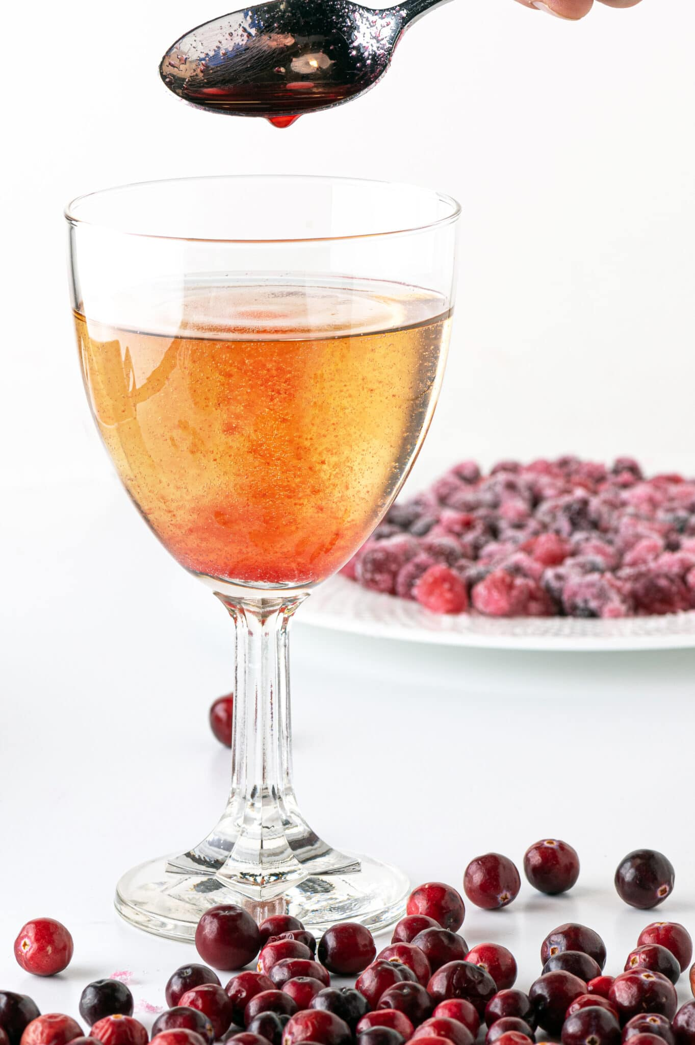 A golden beverage in a wine glass with a stream of cranberry syrup being poured in.   A dish of sugar-free candied cranberries are in the background with fresh ripe cranberries in the foreground.