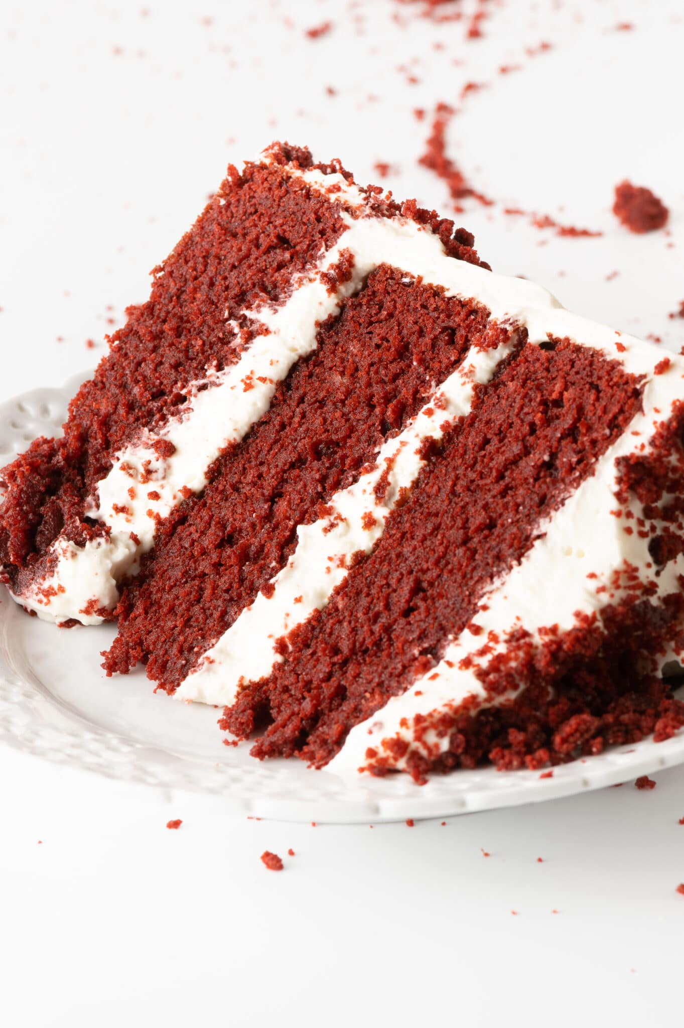 A single slice of bright red maroon red velvet cake with bright white layers of frosting.  The cake is set on a white texture plate and set against a bright white tabletop with red cake crumbs scattered around the plate.