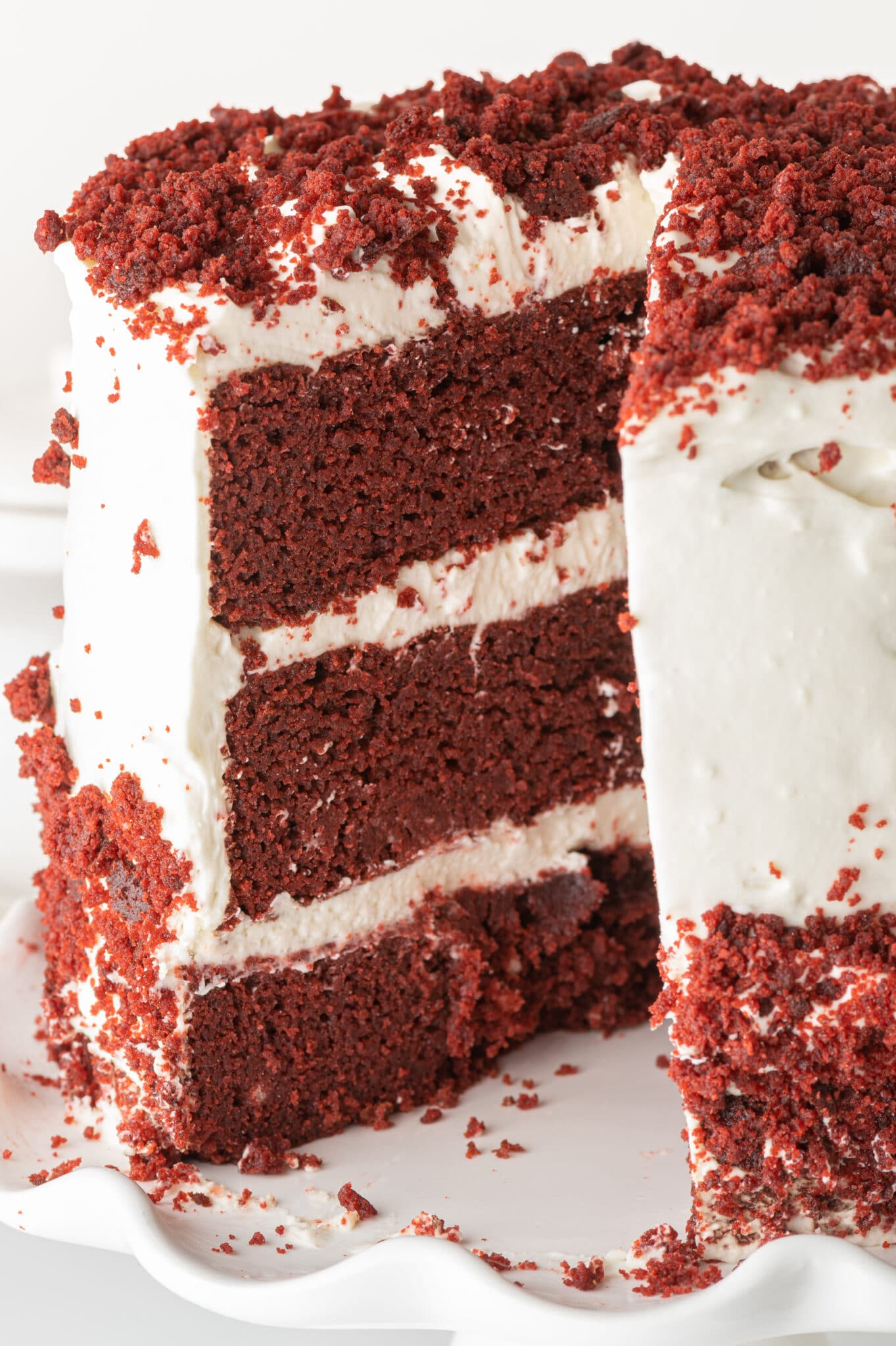 Low carb red velvet cake with white cream cheese frosting.  A slice is a removed and you can see the maroon layers contrasted against the bright white frosting.