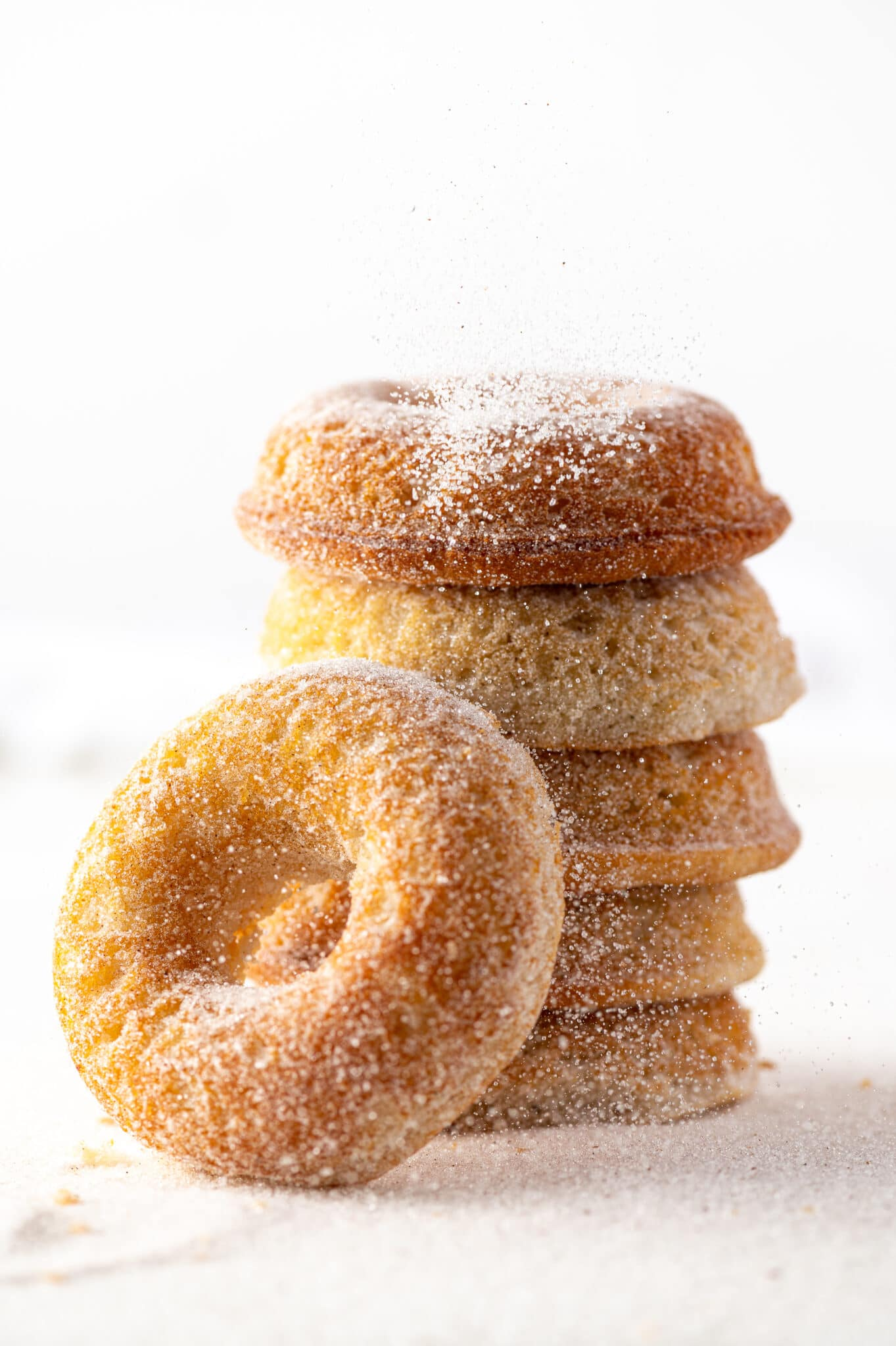 Old fashioned donuts stacked against a bright white background with cinnamon sugar being sprinkled over the top.