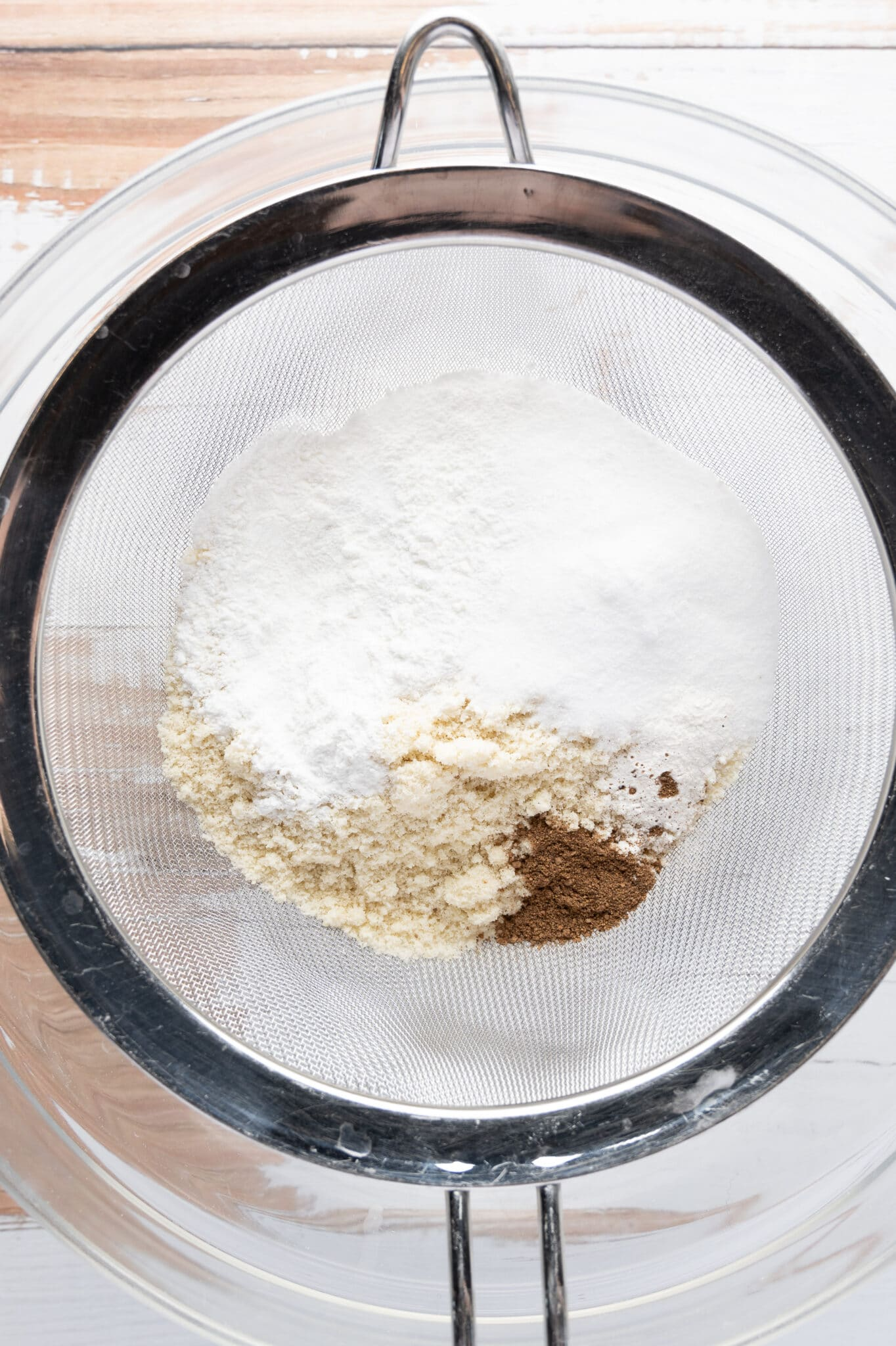 Low carb dry ingredients in a sifter sitting over a clear mixing bowl.