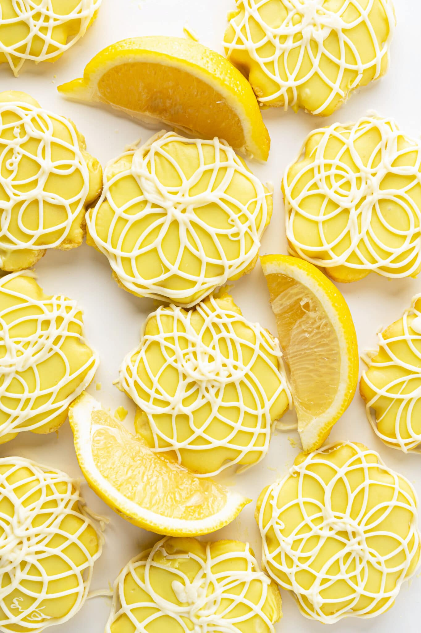 A tray of bright yellow lemon sugar cookies with white chocolate swirls with slices of fresh lemon.
