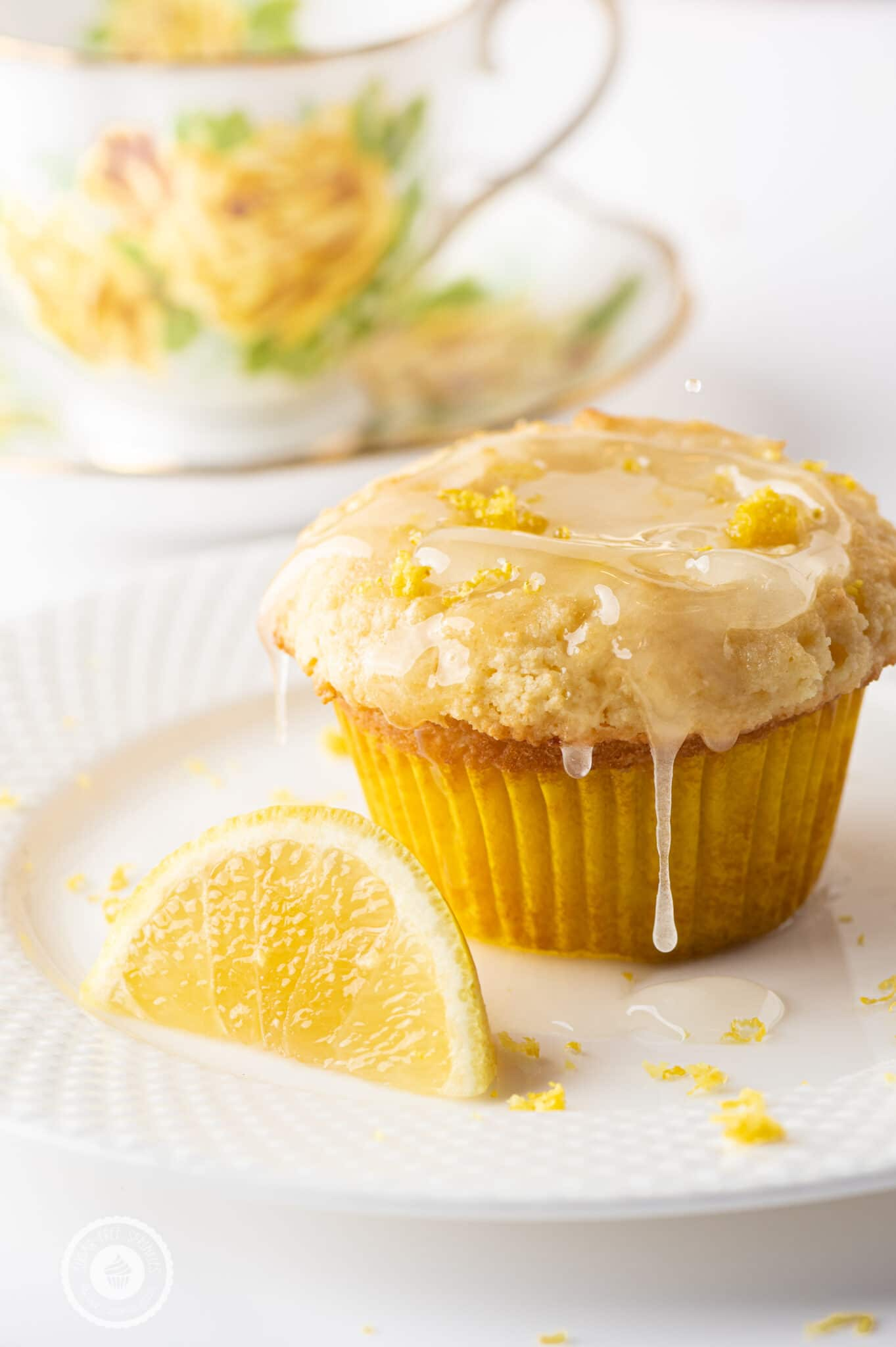 Keto lemon muffin dripping wth sticky lemon glaze on a white plate.  An out of focus yellow rose tea cup is in the background.