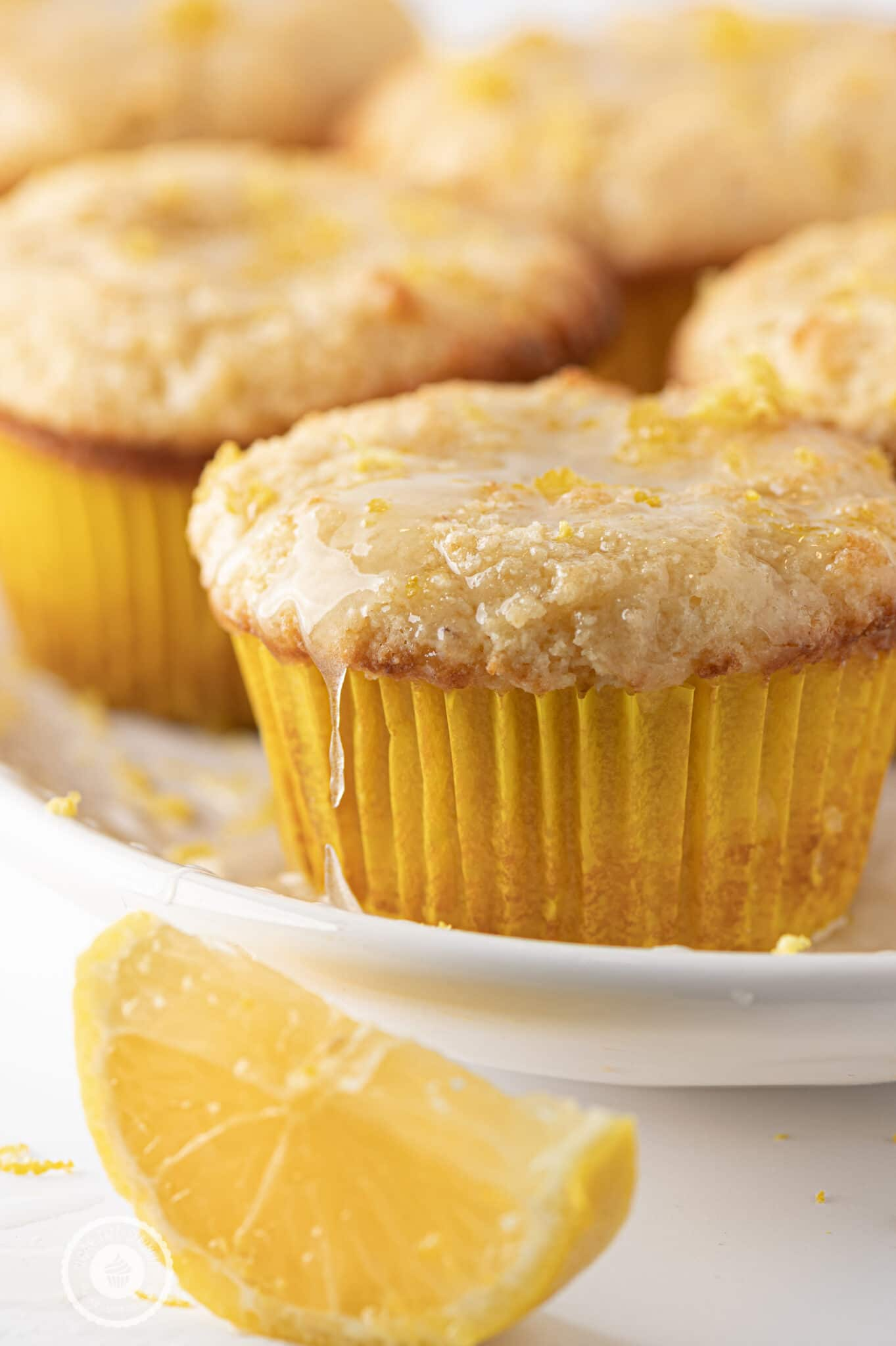 Lemon muffin in a yellow muffin liner, dripping with sticky glaze and topped with fresh lemon rind.  Muffins are stacked in behind slightly out of focus.