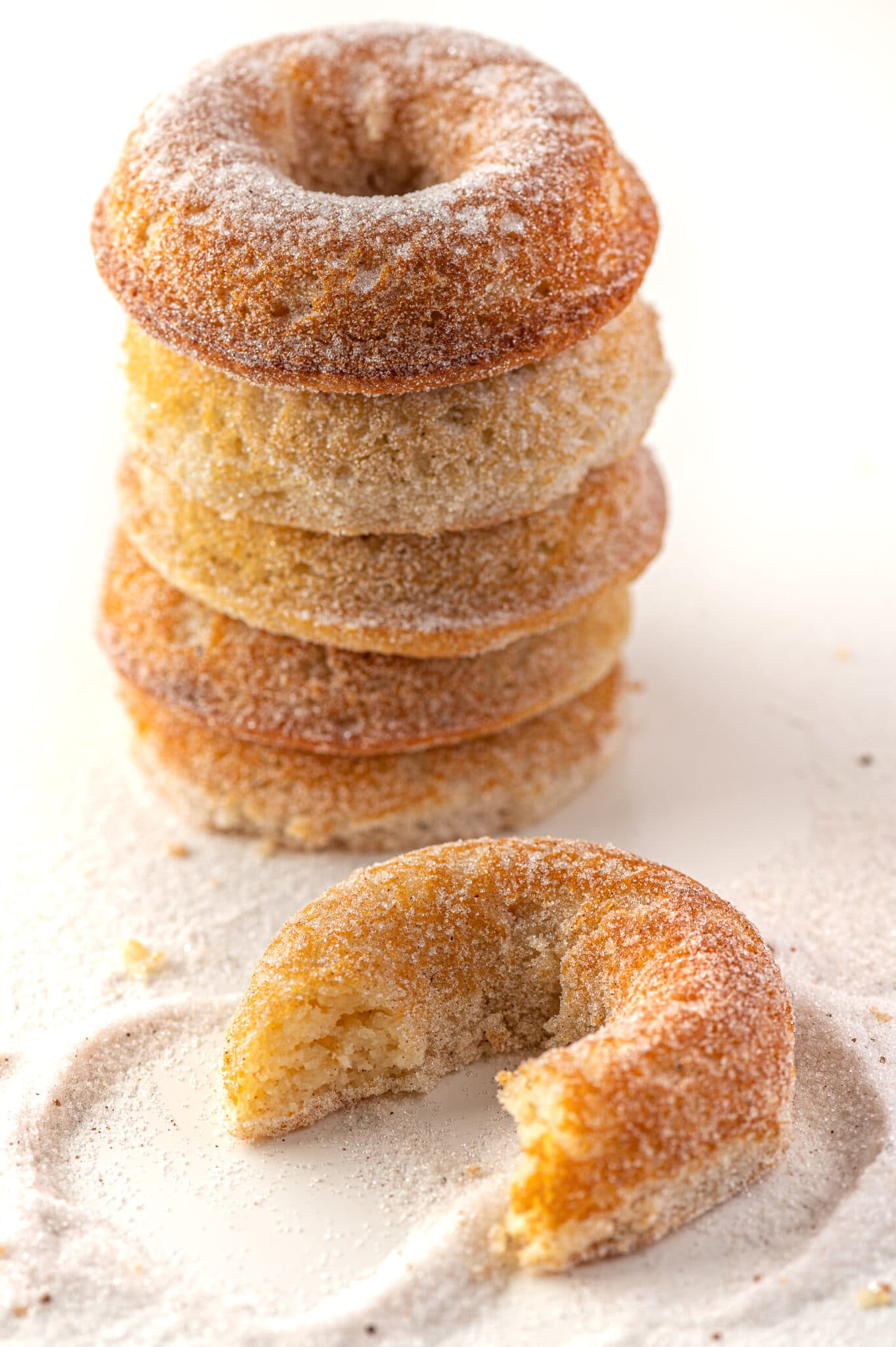 A stack of low carb donuts against a bright white background with sprinkled cinnamon sugar all over the table.