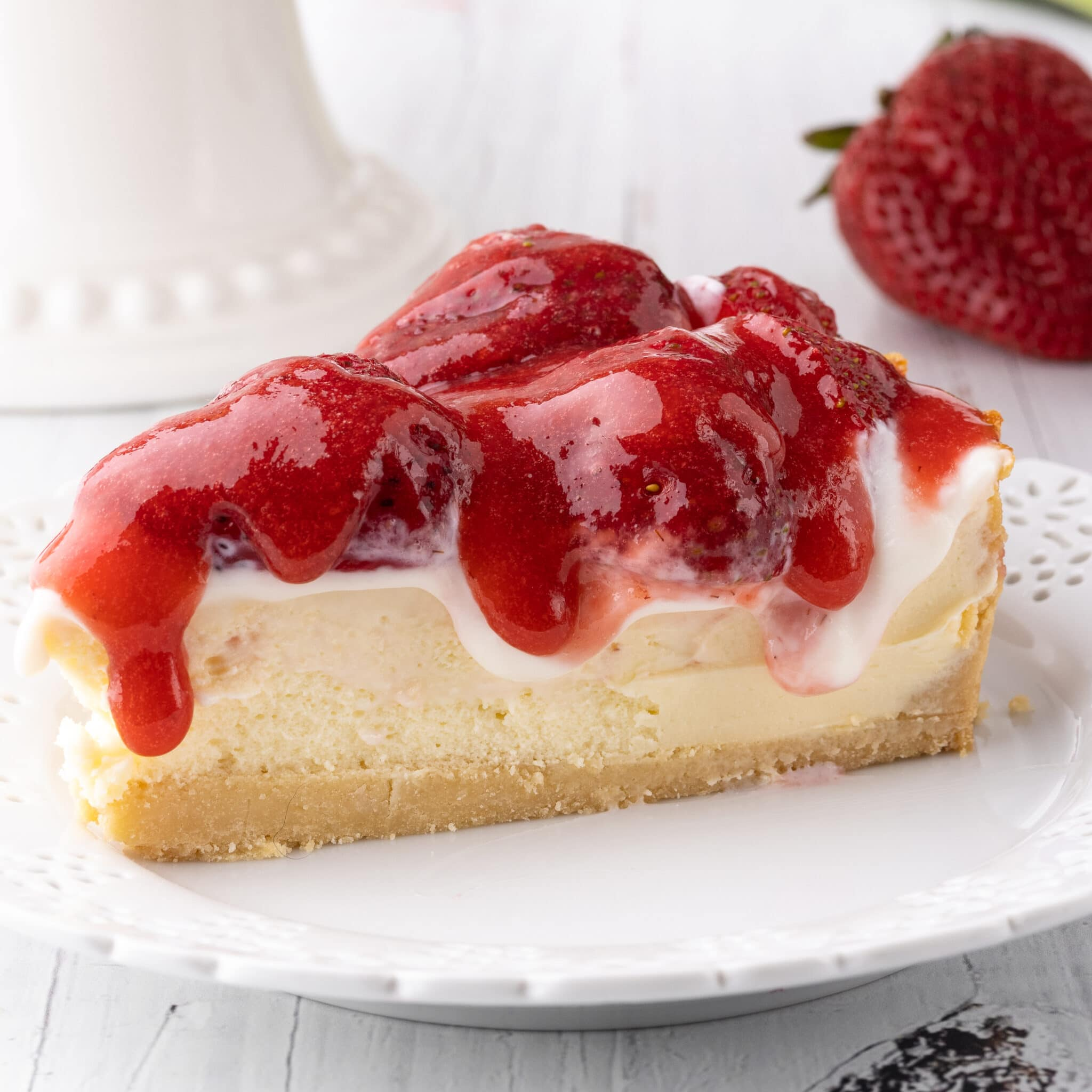 A slice of strawberry cheesecake dripping with sour cream and strawberry sauce topping.