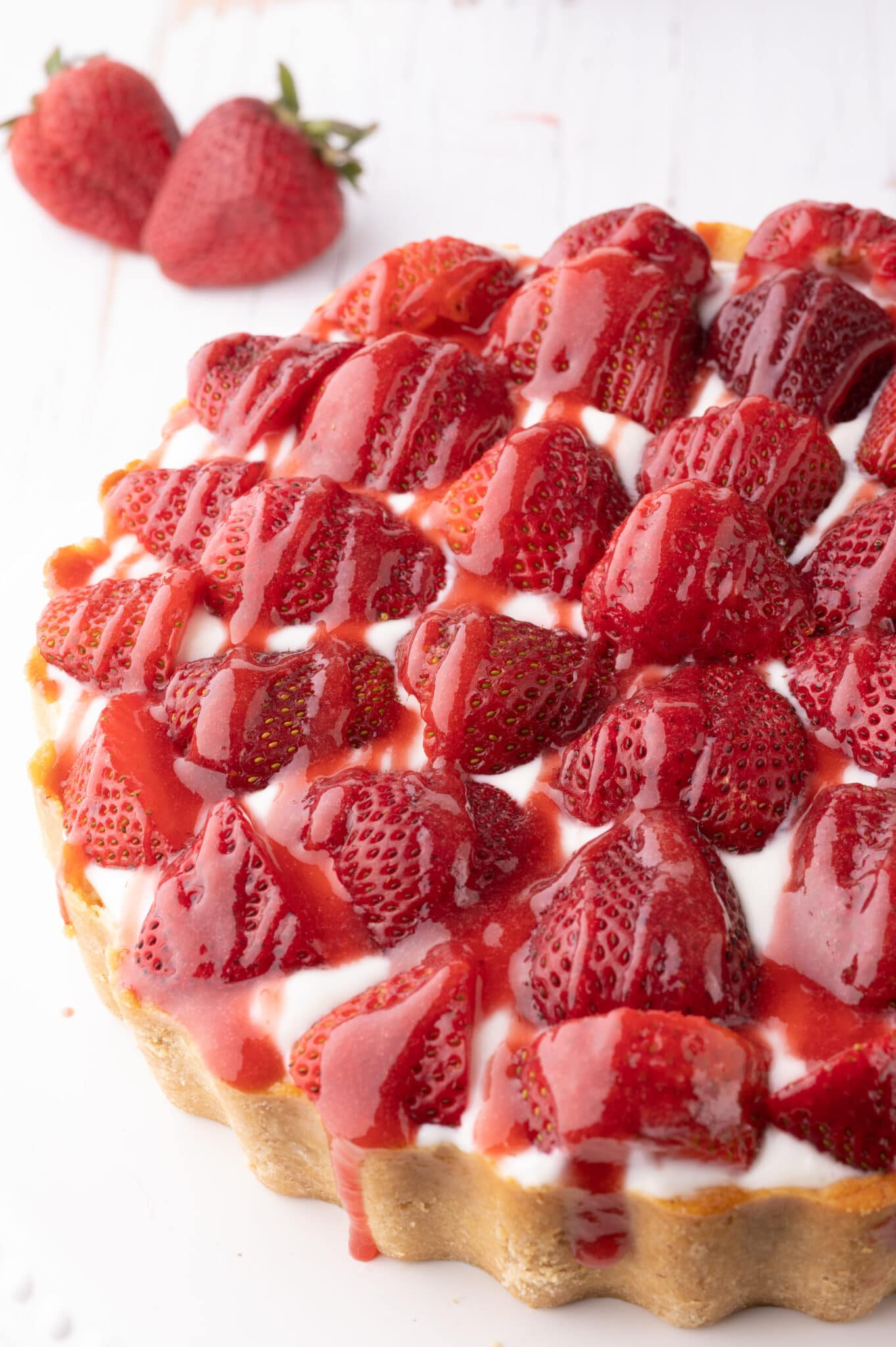 Keto strawberry cheesecake with fresh strawberries and drizzled with strawberry sauce.