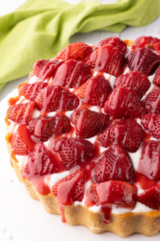 Keto strawberry cheesecake with fresh strawberries and drizzled with strawberry sauce.  The cheesecake rests on a bright white cake stand.