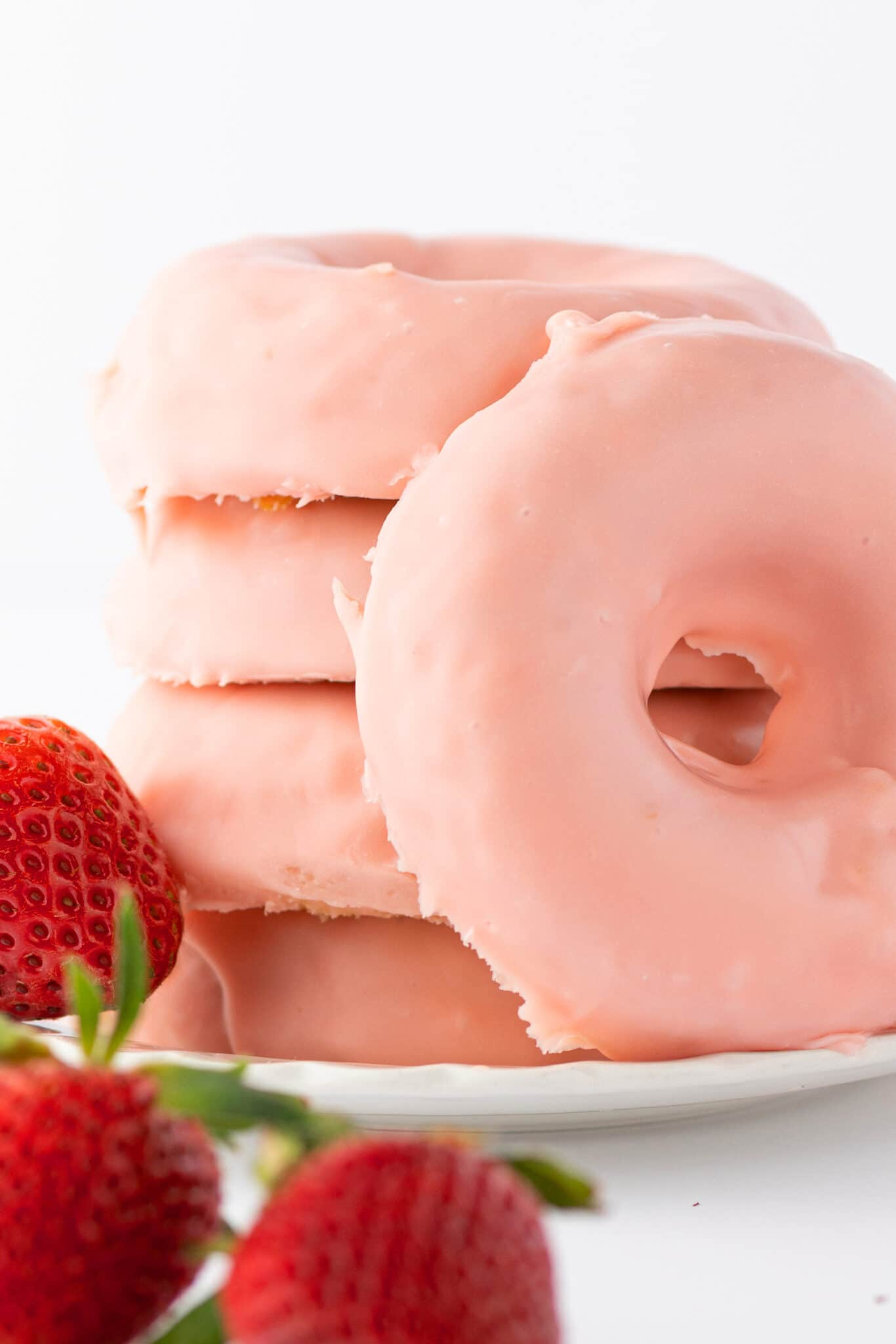 A stack of strawberry glazed donuts on a white plate with fresh ripe red berries scattered around the tabletop.