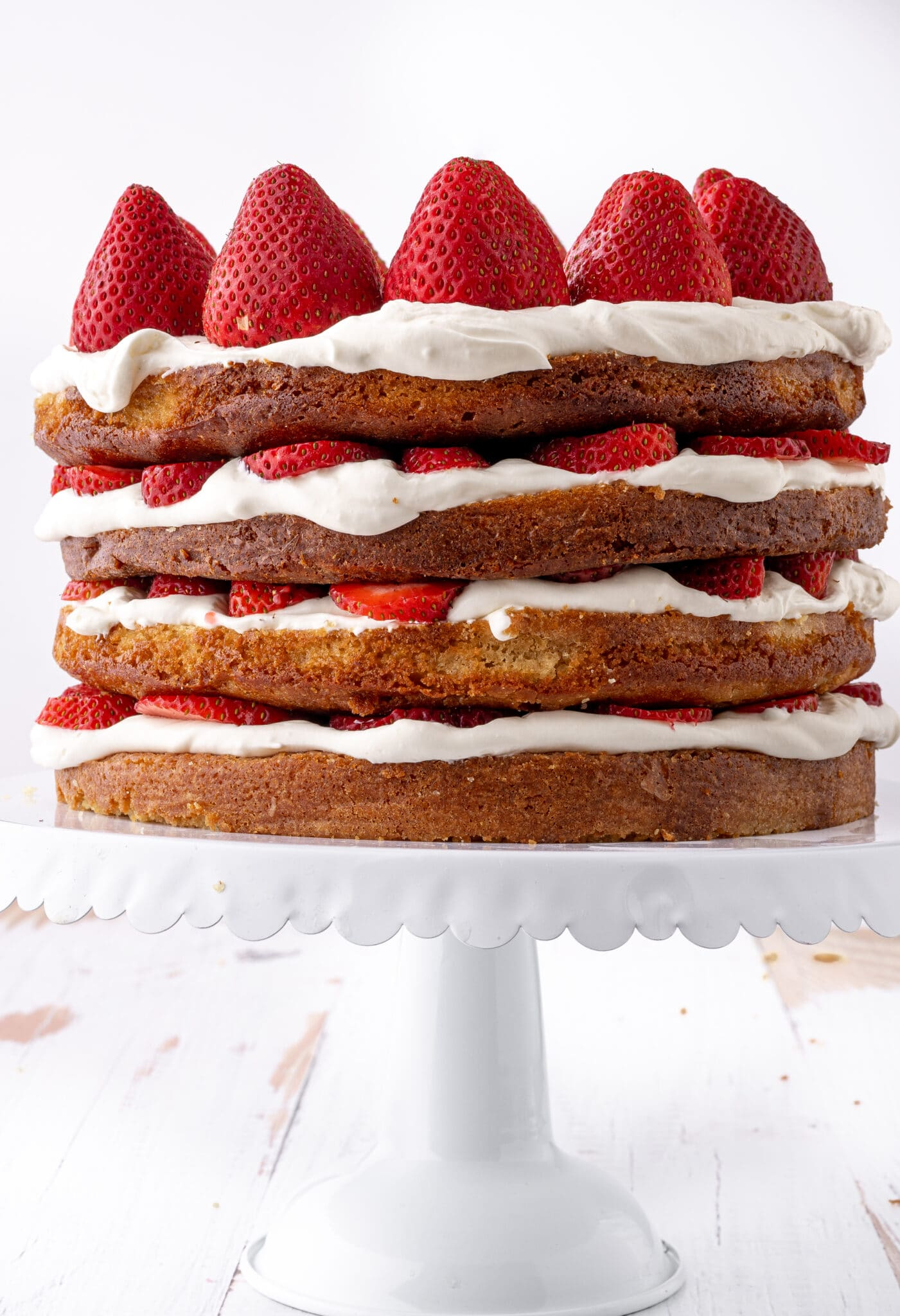 A four layer low carb strawberry shortcake  sliced with fresh strawberries and whipped cream on a white ruffled cake stand.