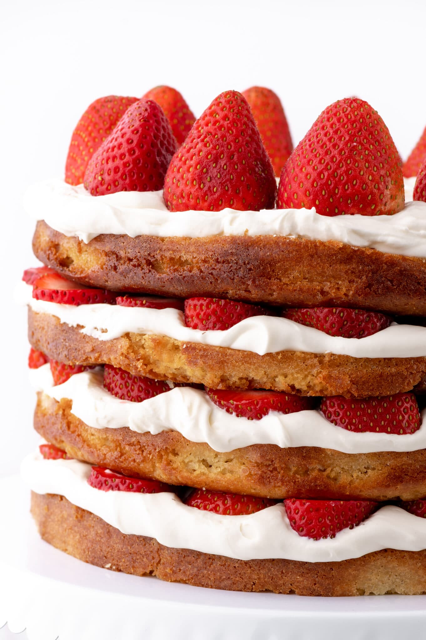 A four layer keto strawberry shortcake with fresh strawberries and whipped cream against a bright white background.