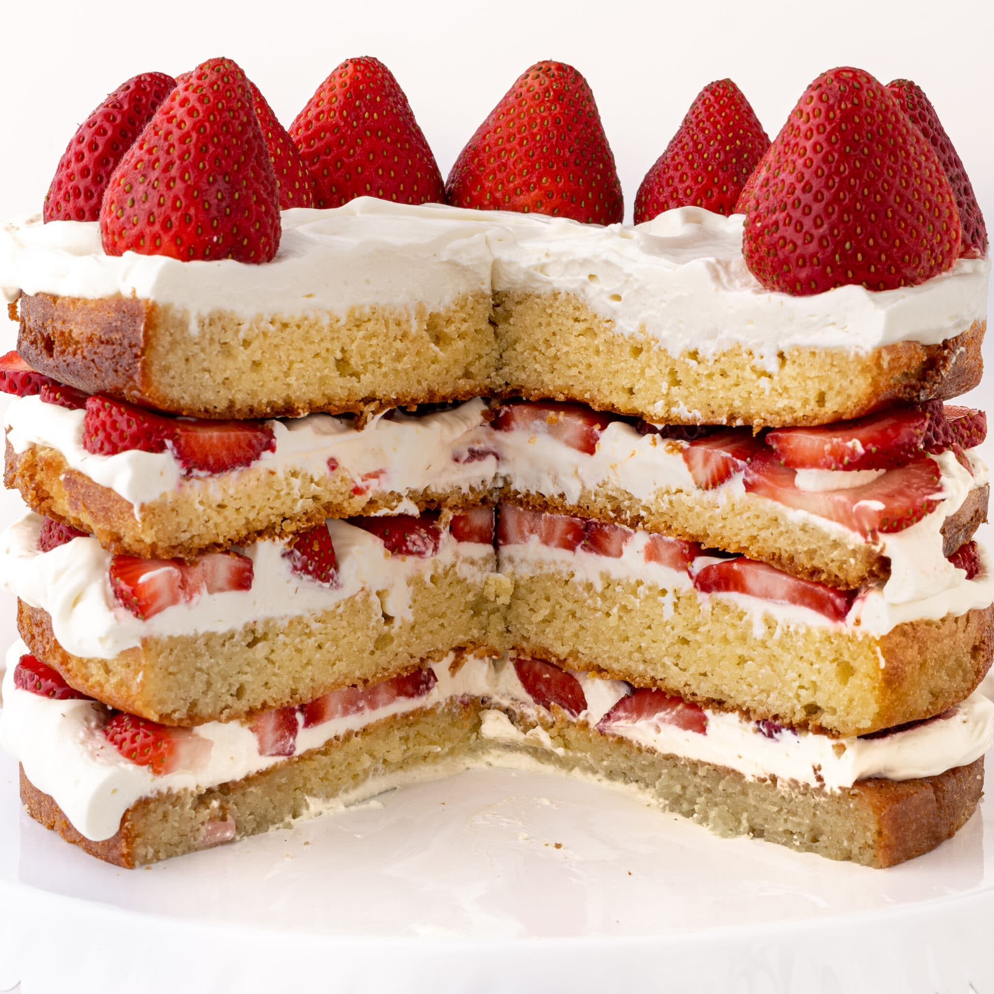 A four layer keto strawberry shortcake  sliced with fresh strawberries and whipped cream against a bright white background.