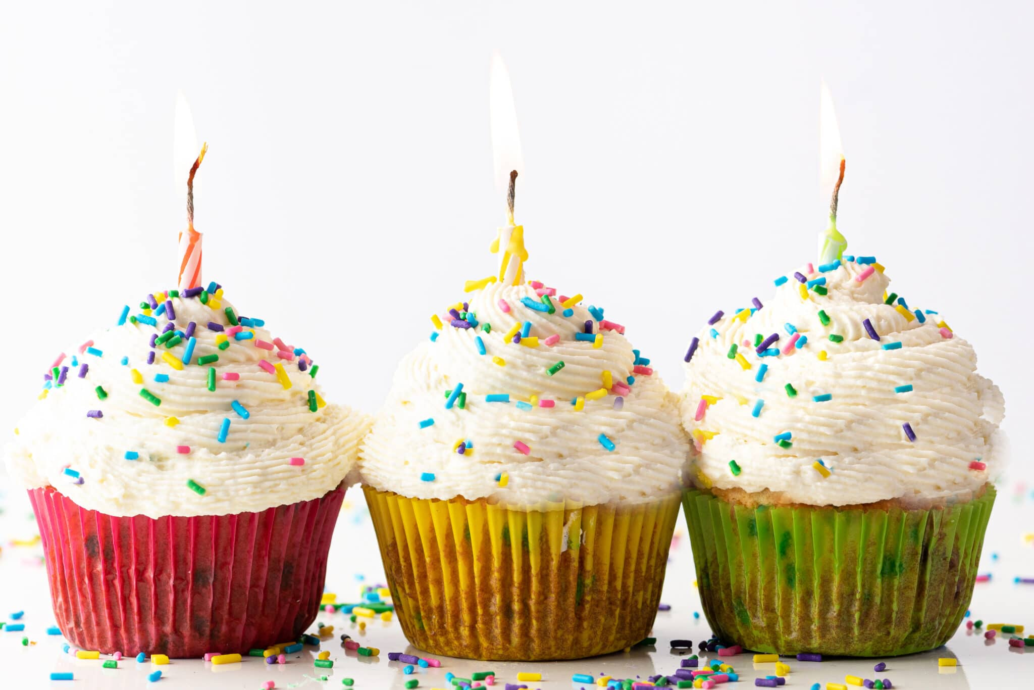 Three vanilla frosted cupcakes in colorful cupcake wrappers.  The cupcakes have cheerful sprinkles and lit birthday candles.