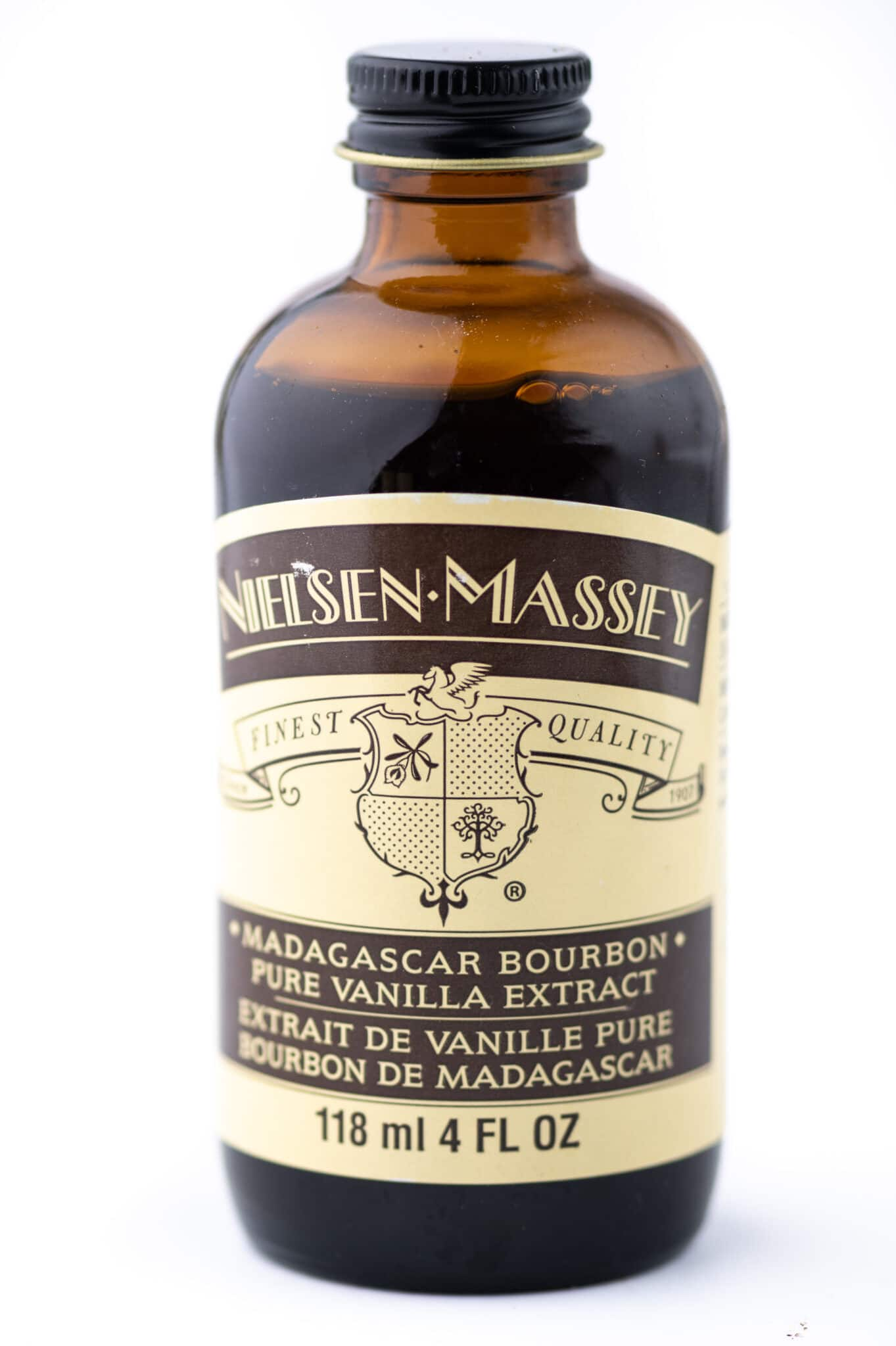 A bottle of Madagascar vanilla with a red label against a bright white background.