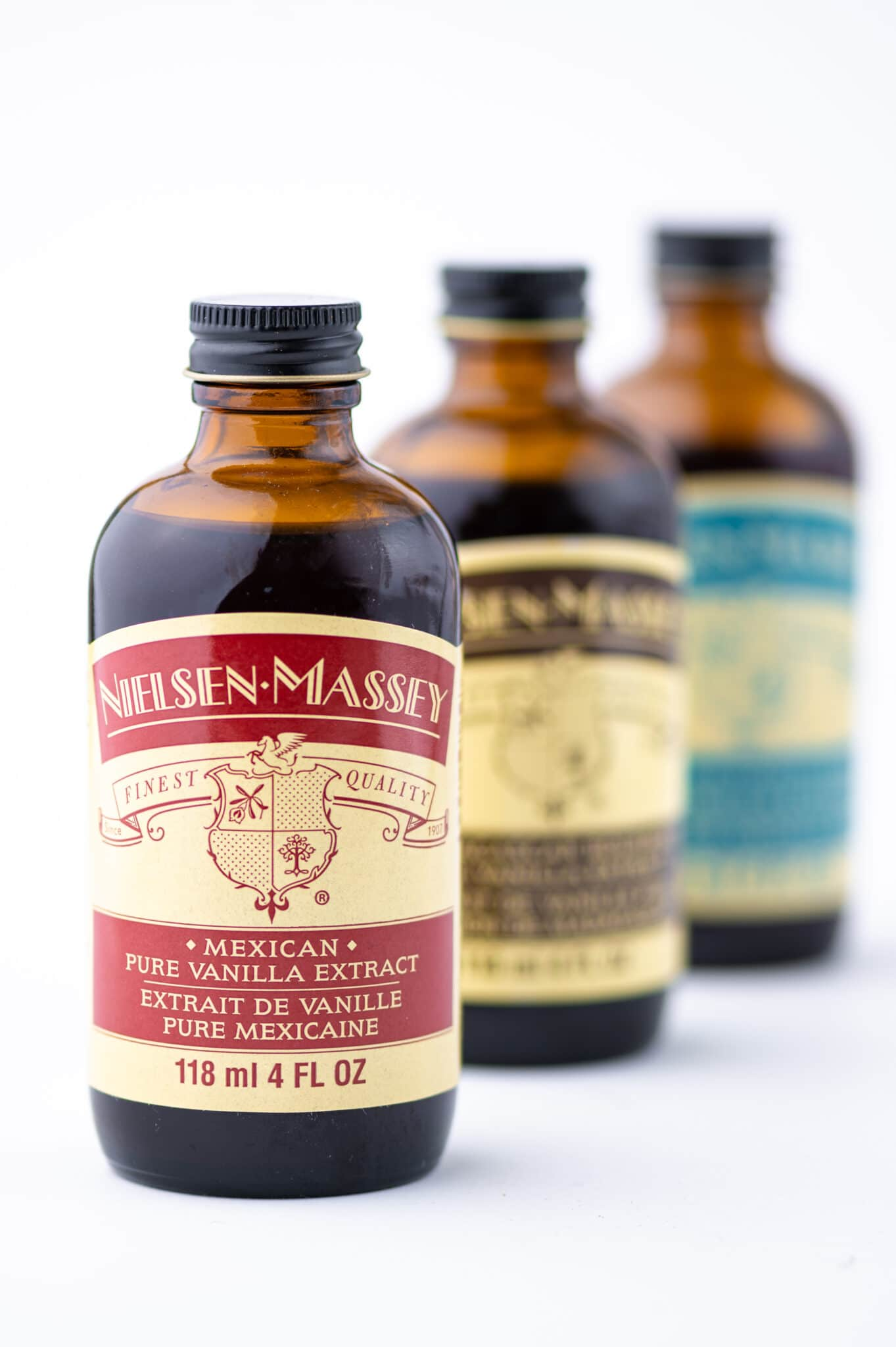 Three different bottles of vanilla against a bright white background.